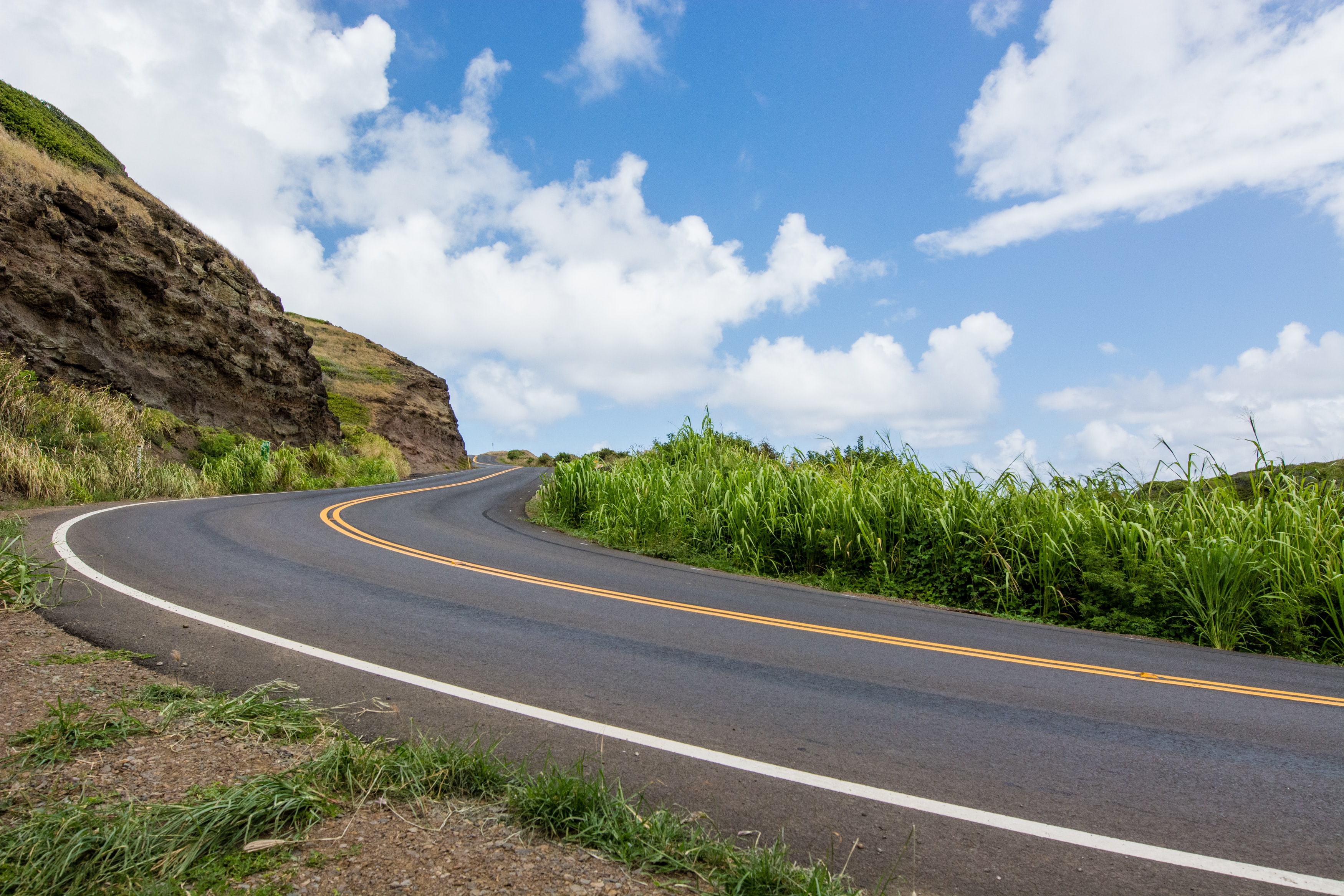 A winding road along the side of a cliff and grass on the other side in Maui