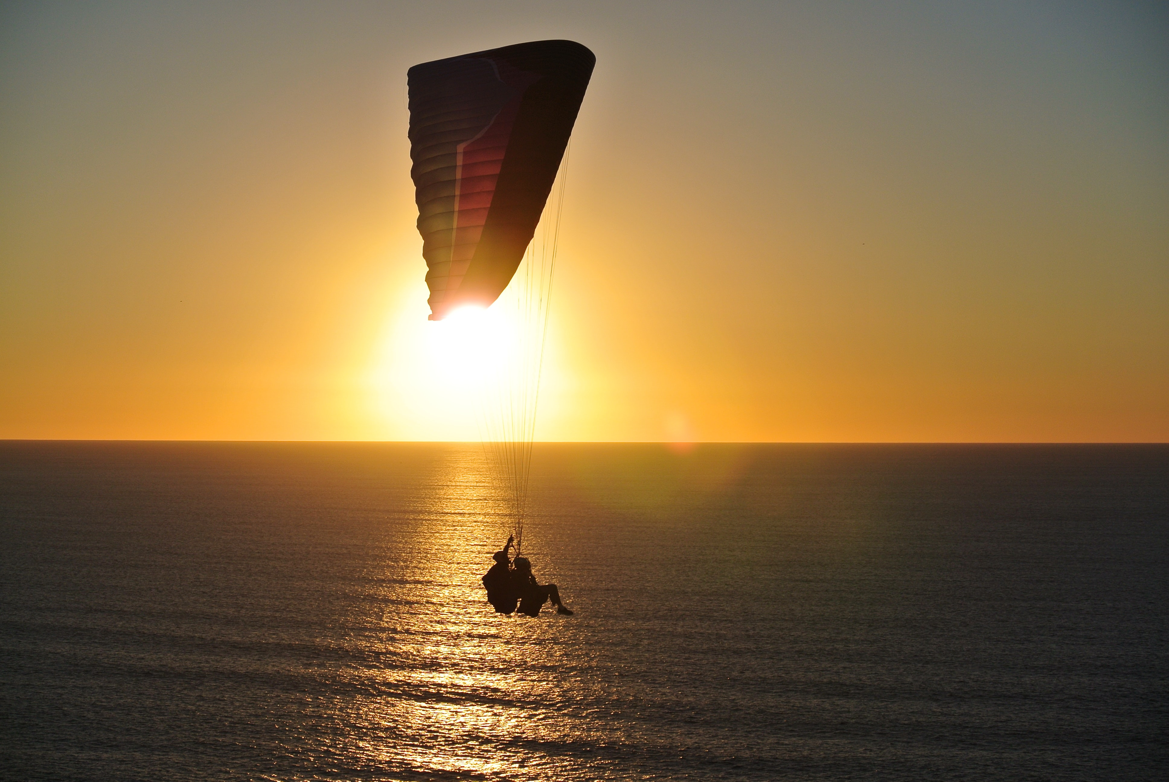 person in parachute above body of water during golden hour