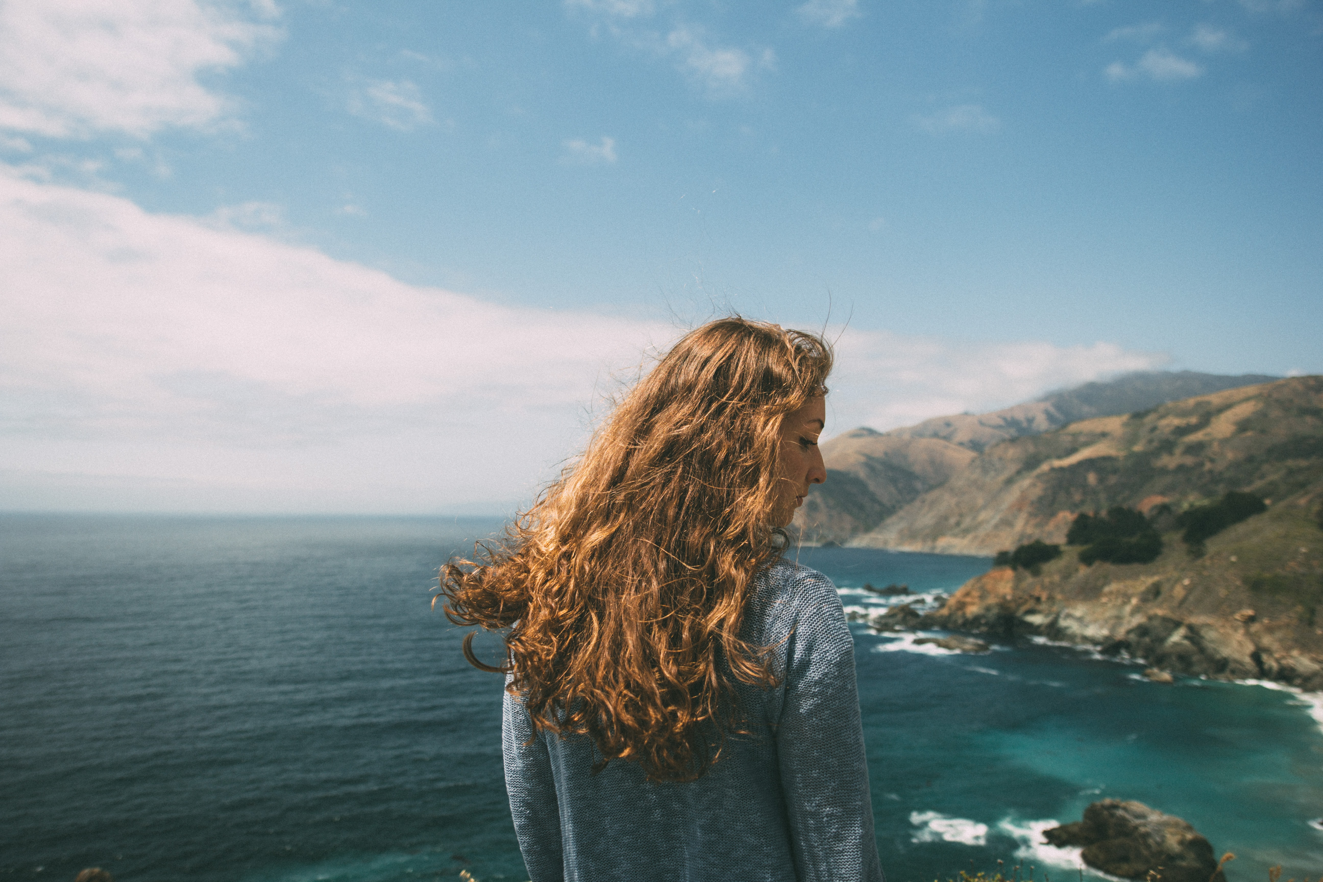 woman standing facing the ocean during daytime