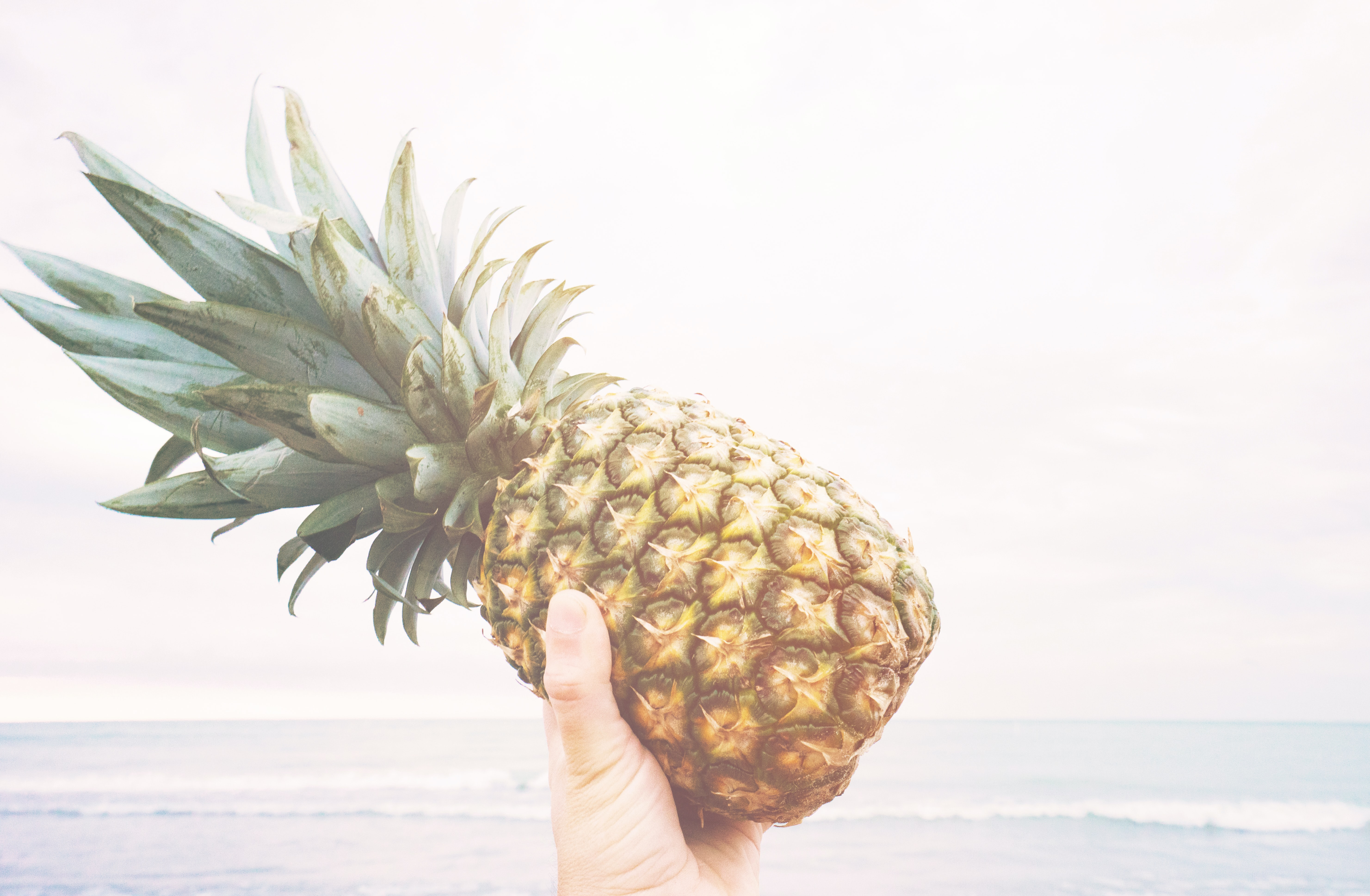 Holding a pineapple at the beach.