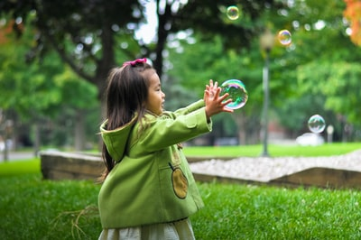 selective photo of a girl holding bubbles child zoom background