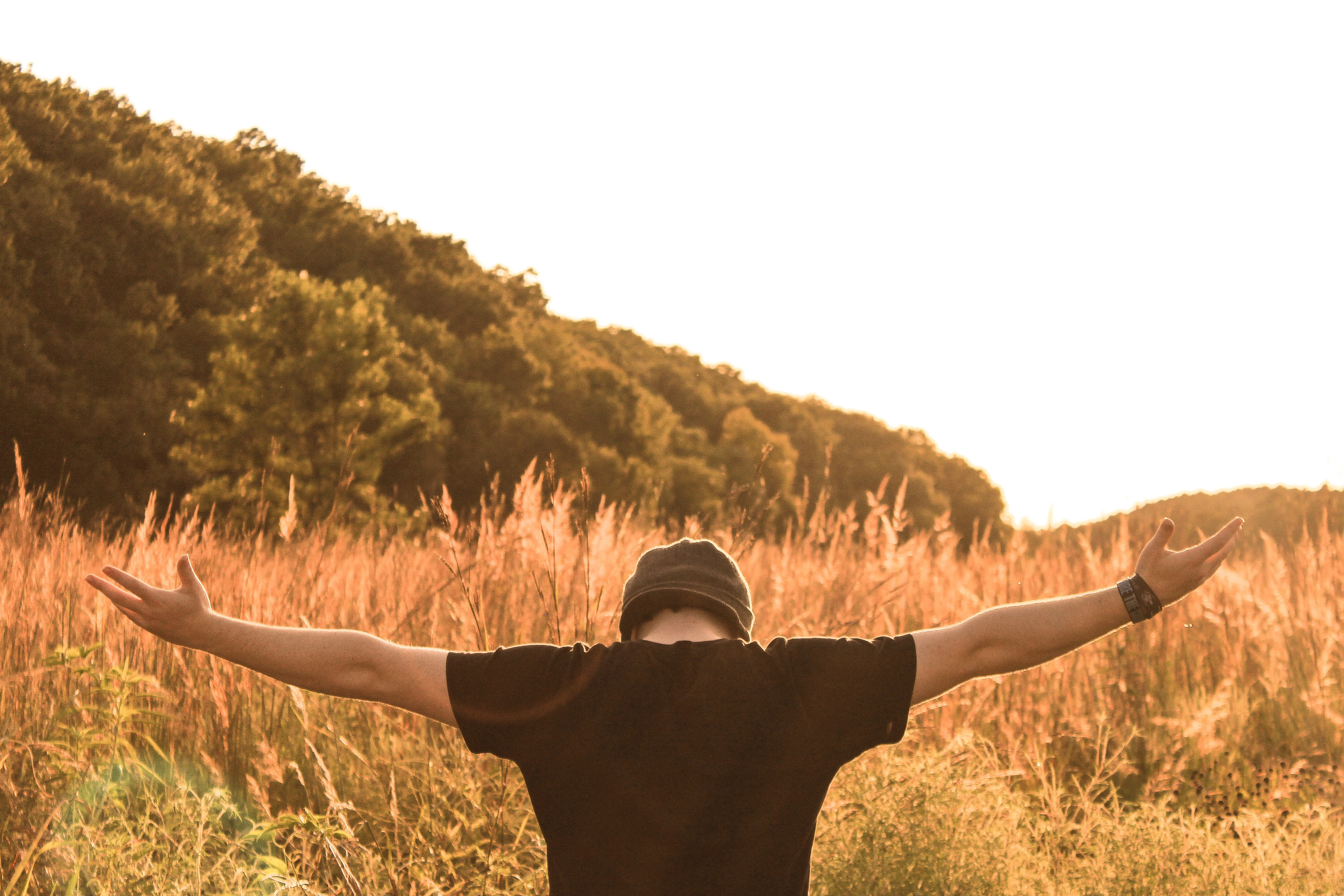 A man with a hat on, standing in a field in the countryside with his arms stretched out