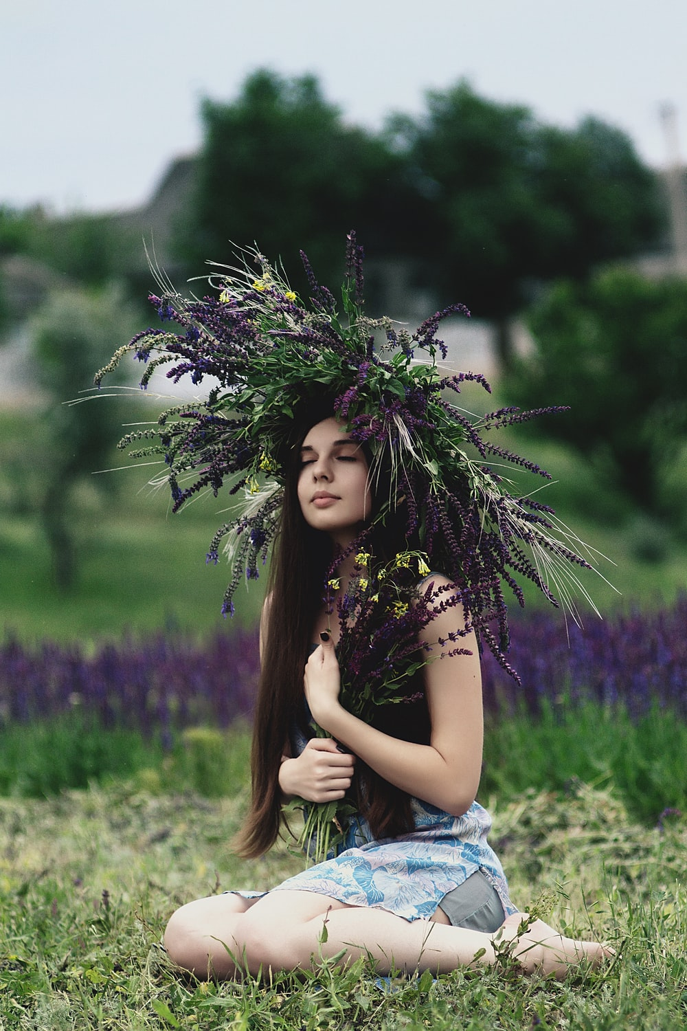 woman wearing lavender headdress sitting on grass