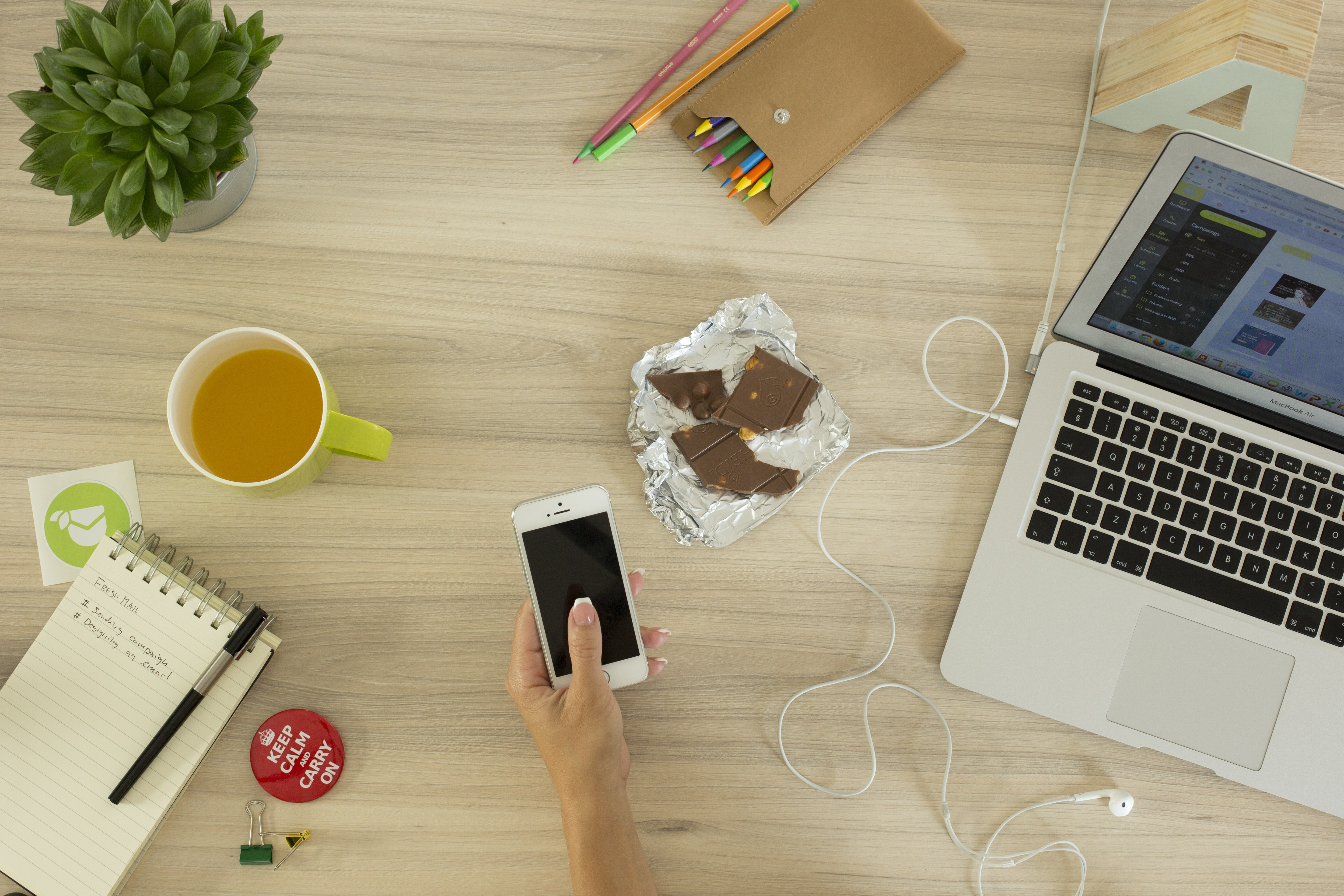 A woman's hand holding a phone over a busy surface with a laptop, a cup of tea and a half-eaten chocolate bar