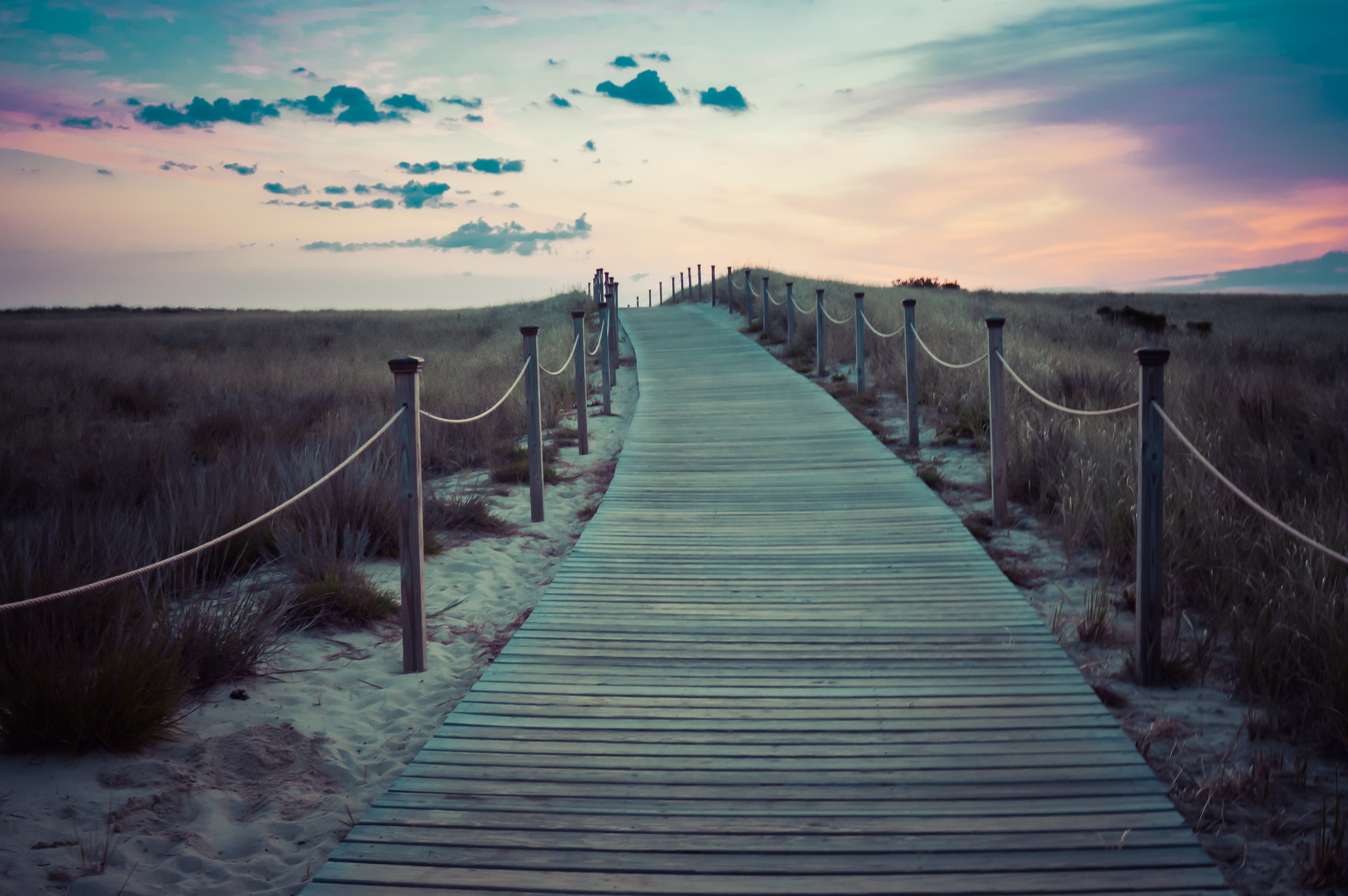 Wooden boardwalk with rope fence through the grass field after the sunset