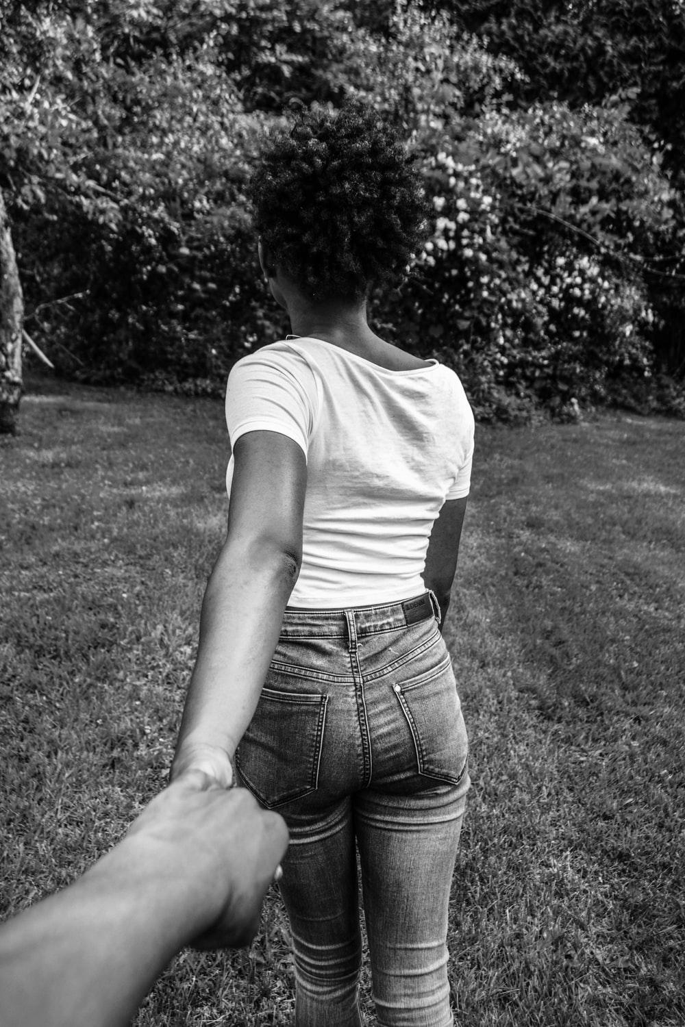 greyscale photography of woman walking with hand at the back holding other hand