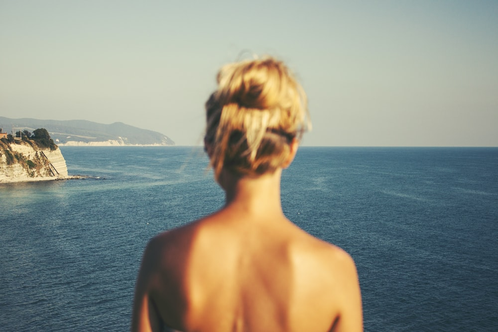 topless woman standing facing blue sea under white sky