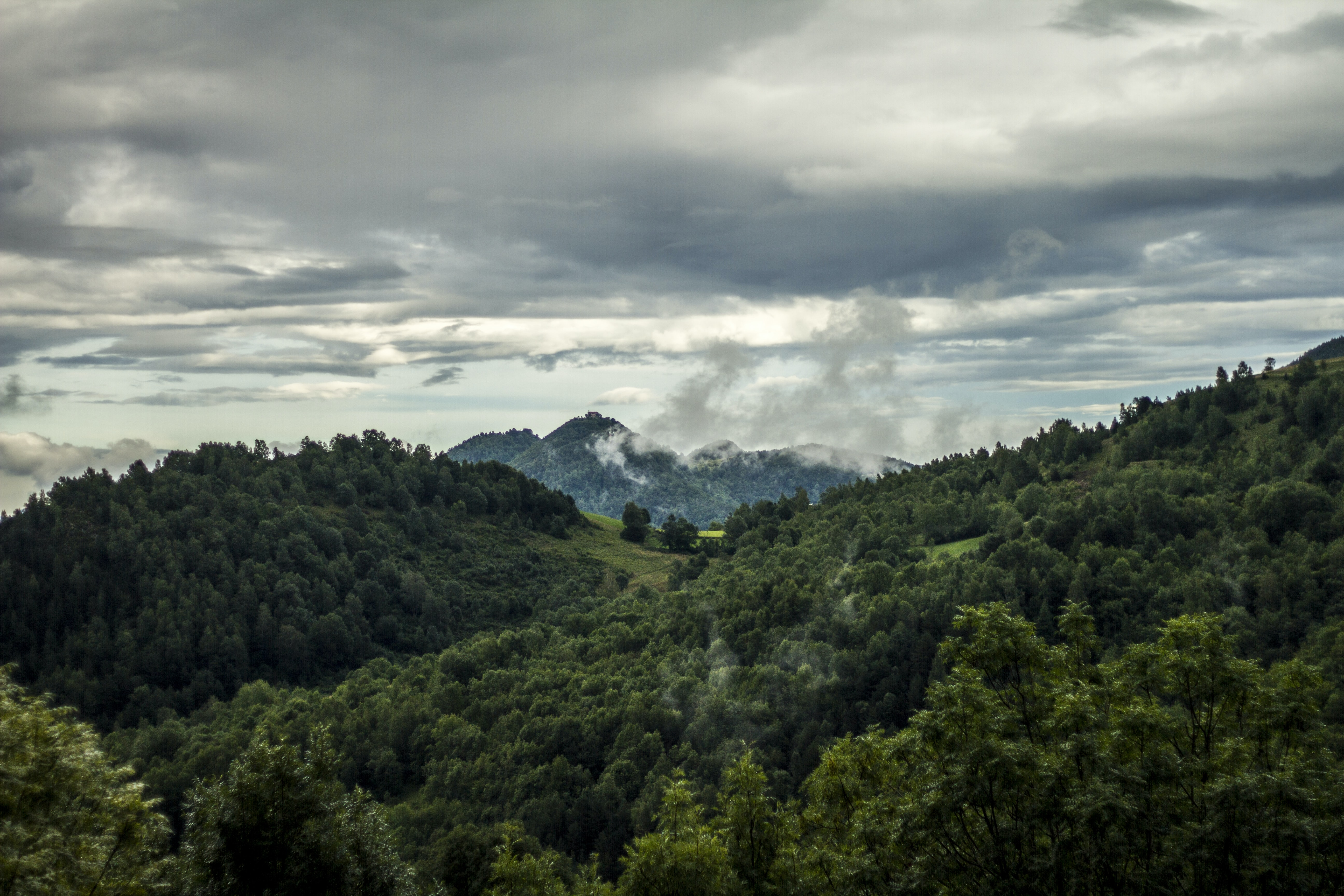 Thick gray clouds over wooded hills in Abella