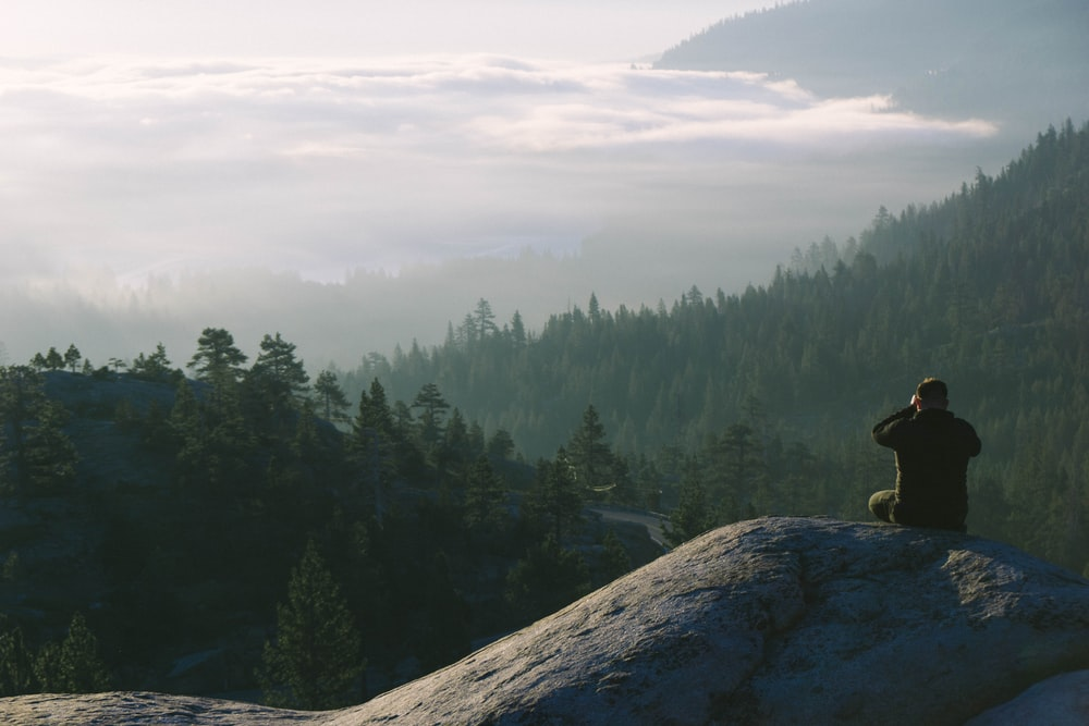 man sits on the mountain facing landscape view