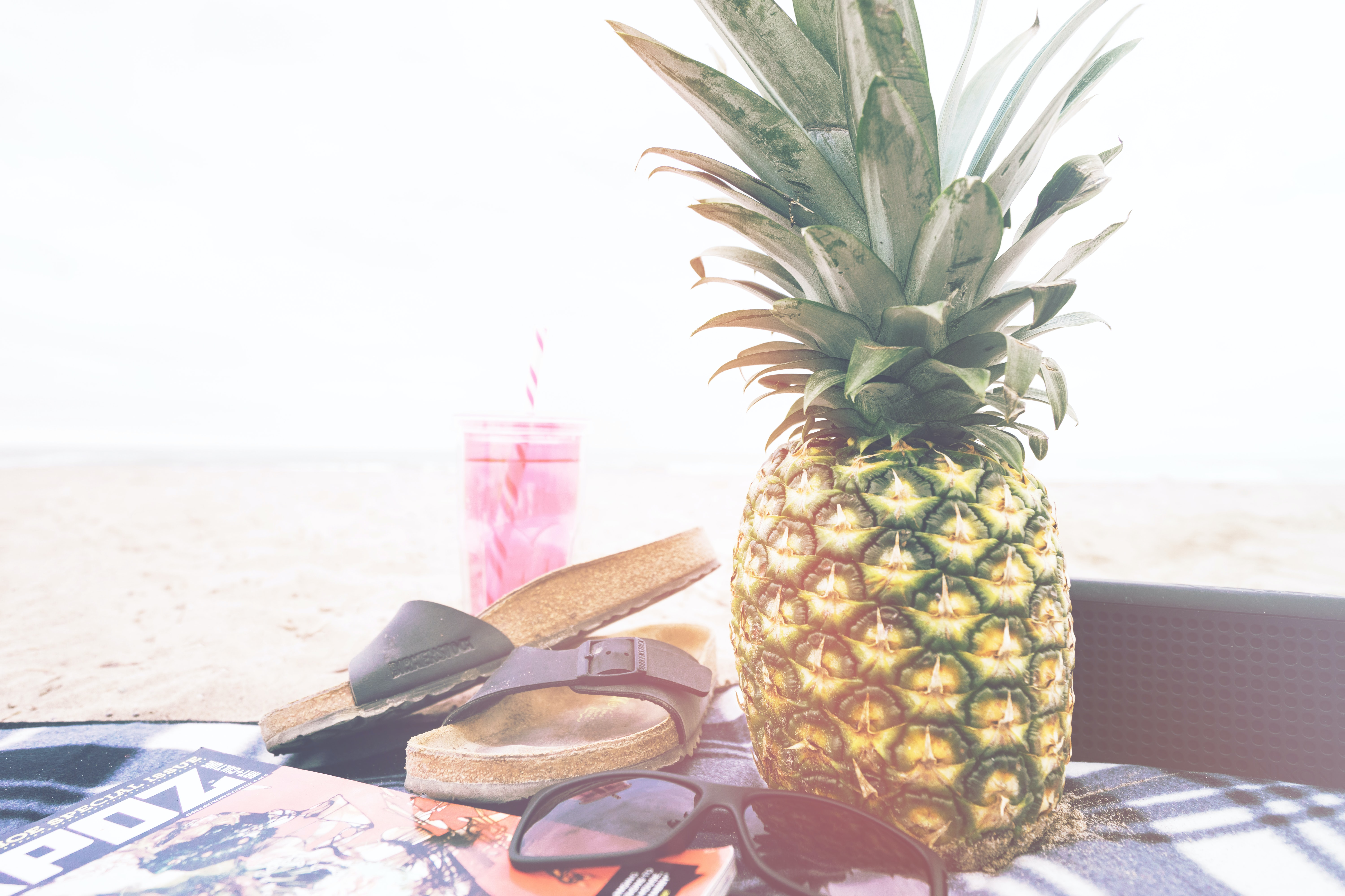Capture of a juicy looking pineapple beside a sandal with pink sunglass and magazine Port Stanley