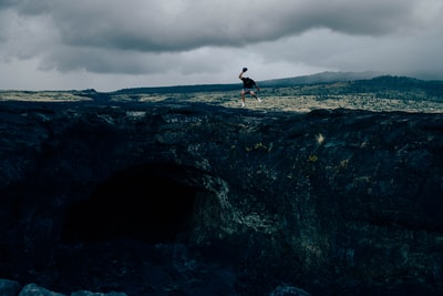 man standing on rock formation during daytime atmospheric teams background