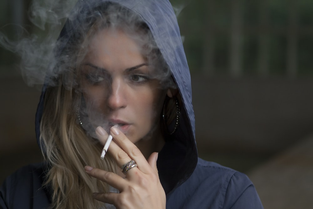 woman wearing hoodie while holding cigarette