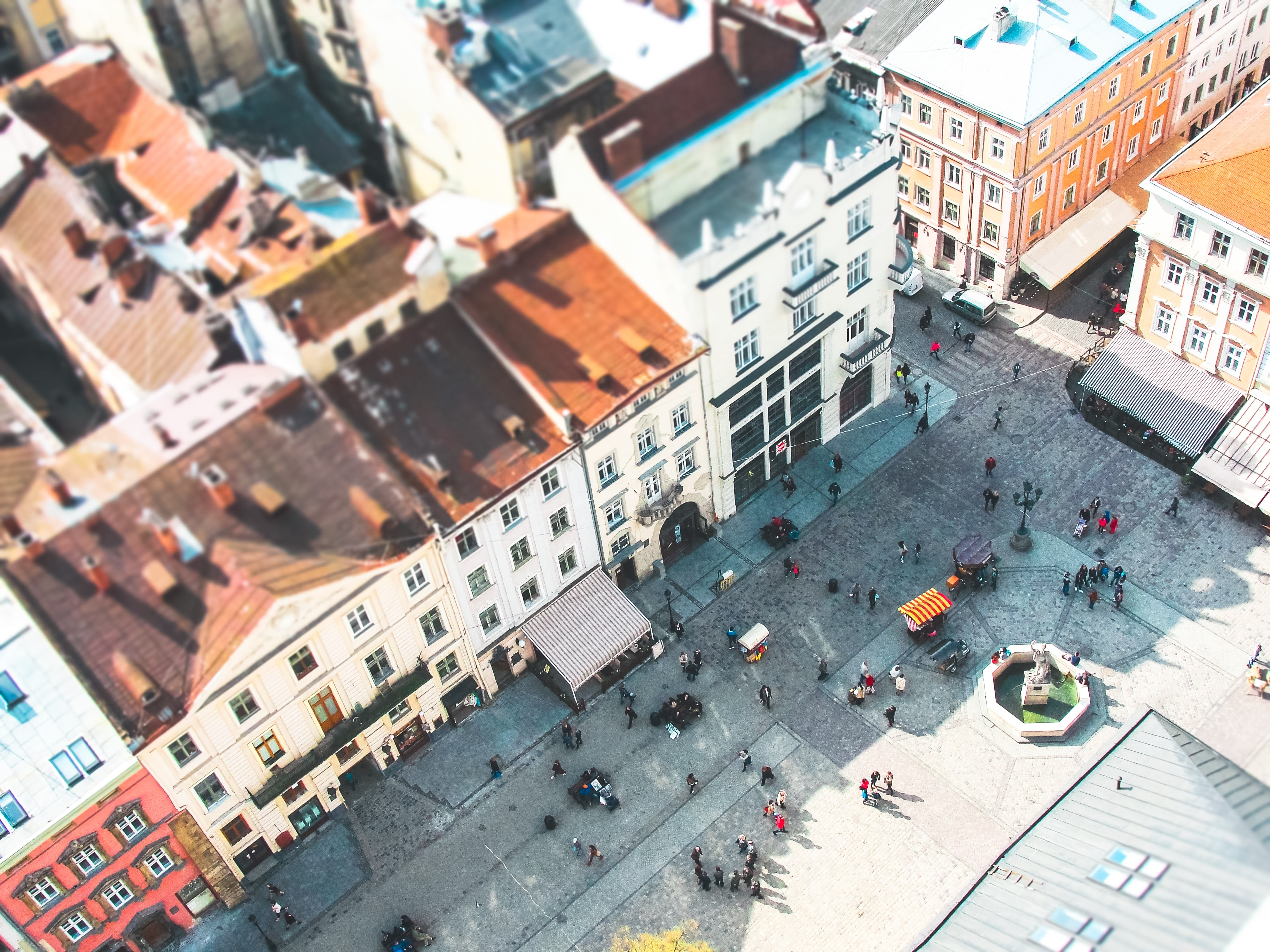 Tilt-shift aerial shot of busy courtyard and colorful buildings in Rynok Square