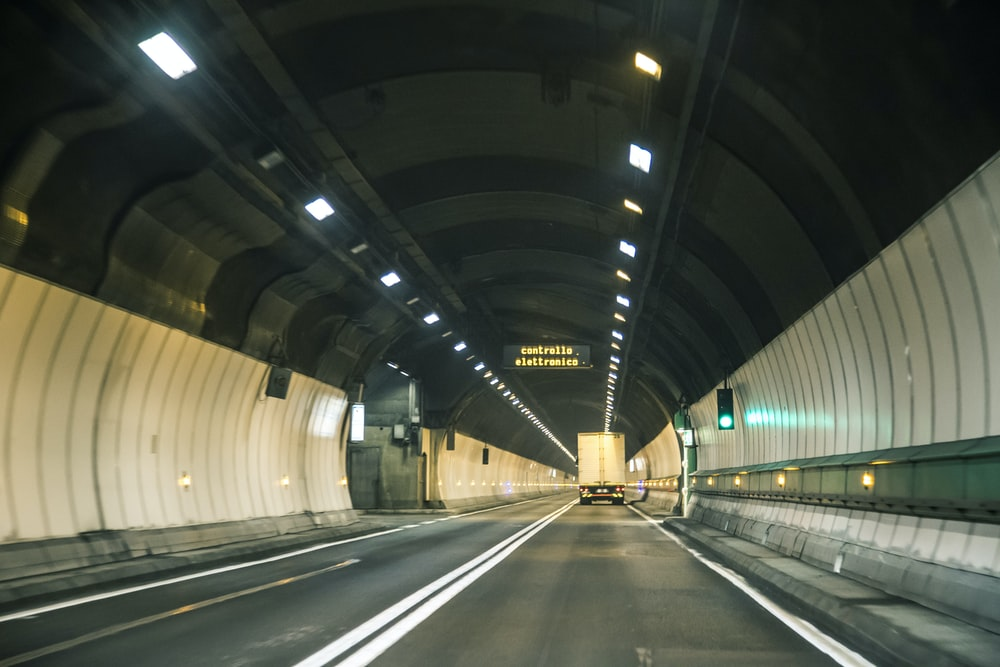 gray and white tunnel with lights turned on during night time