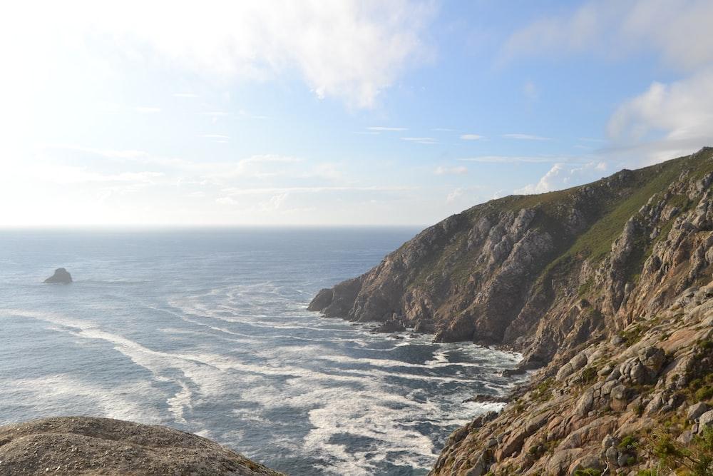 sea hitting seashore beside brown rock mountains under blue sky