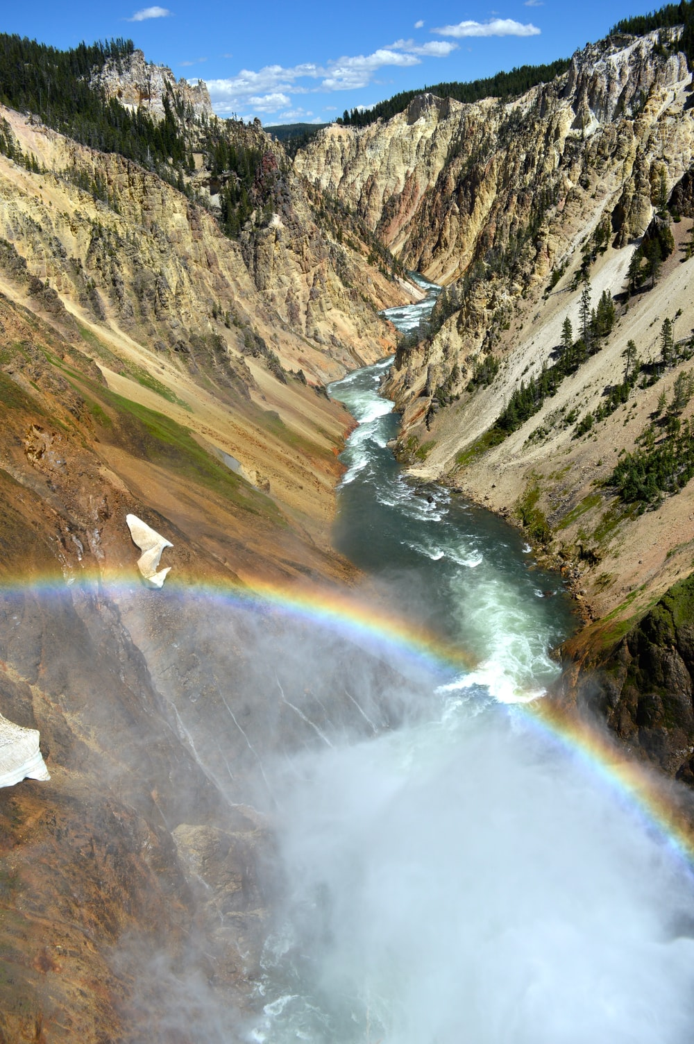aerial photography of narrow river with forming rainbow