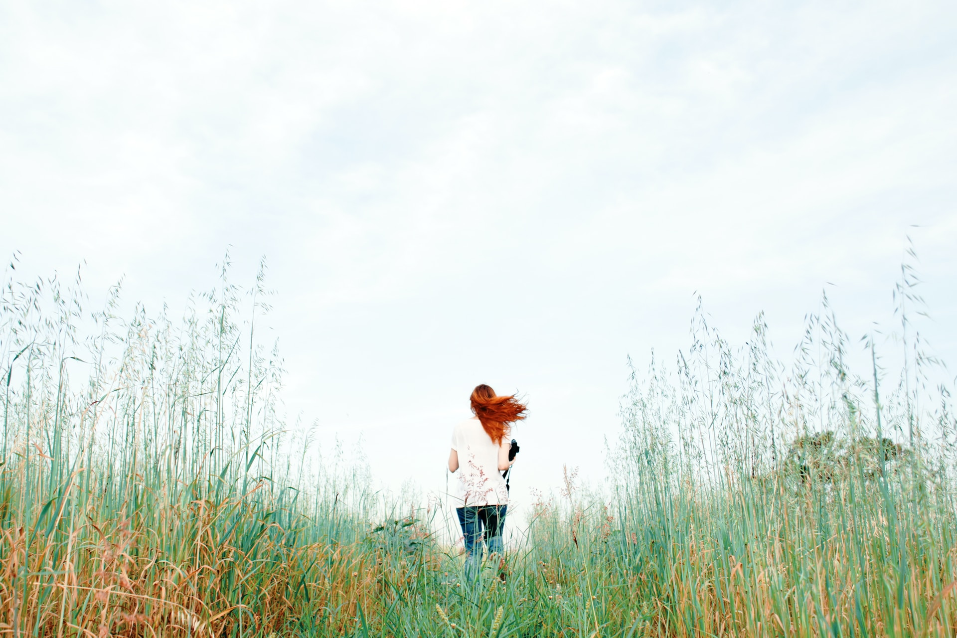 woman standing on green grass field during daytime