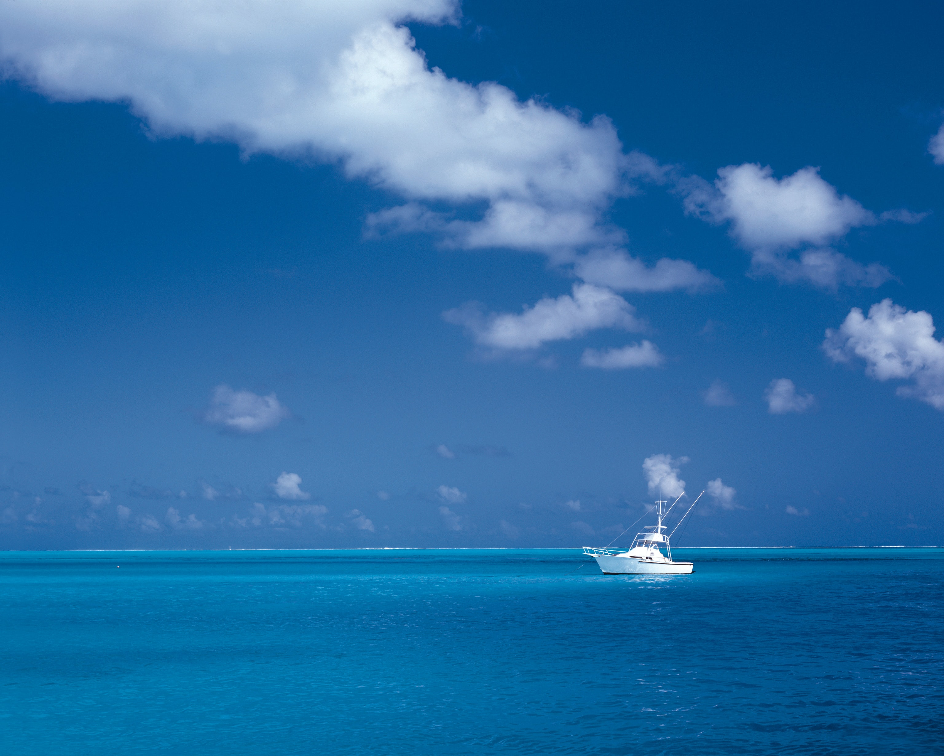 white boat on sea under cloudy sky