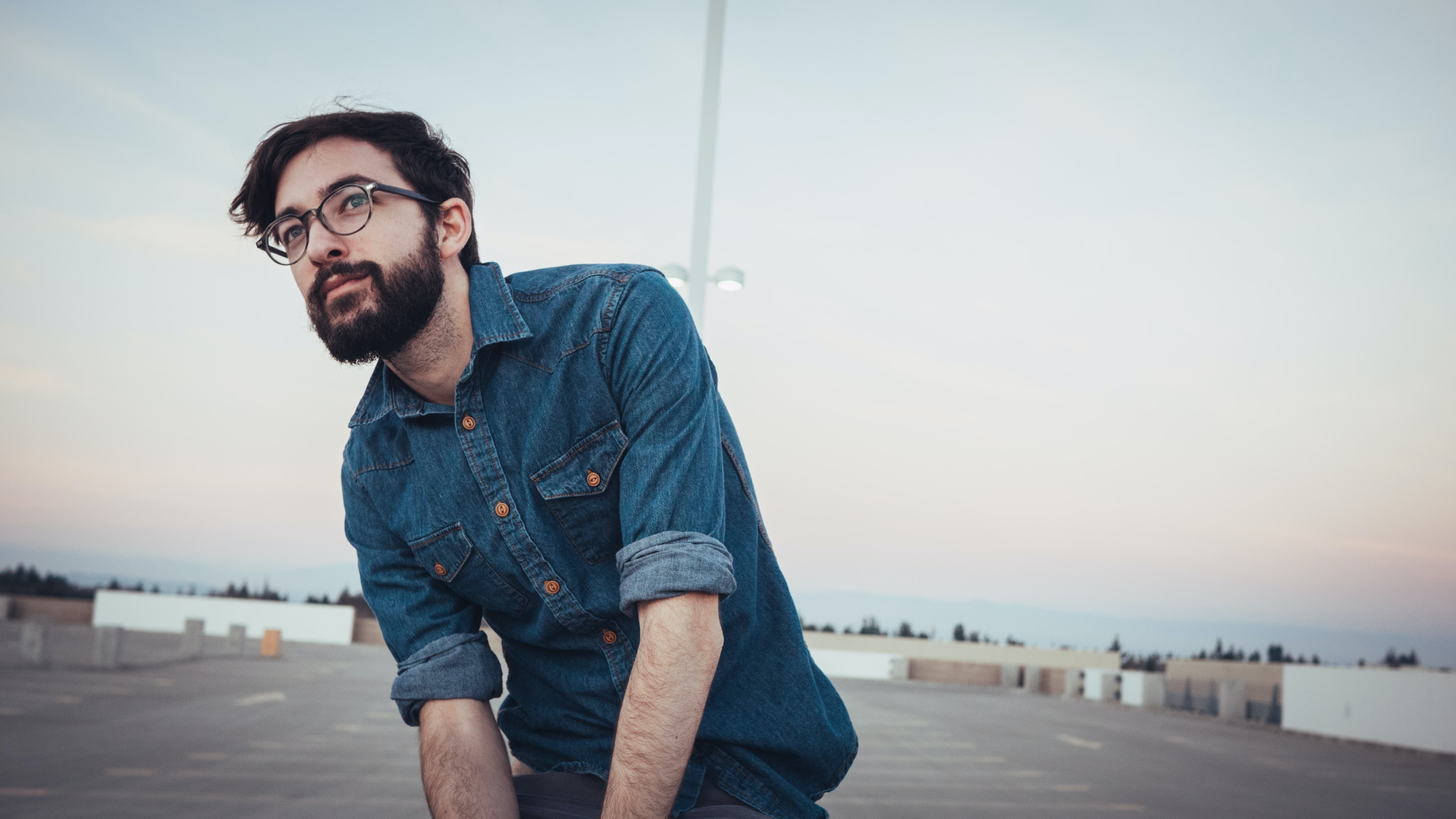 man wearing denim sport shirt and sunglasses on concrete flooring