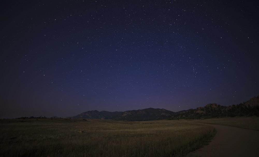 green grass field near mountain at night time photo