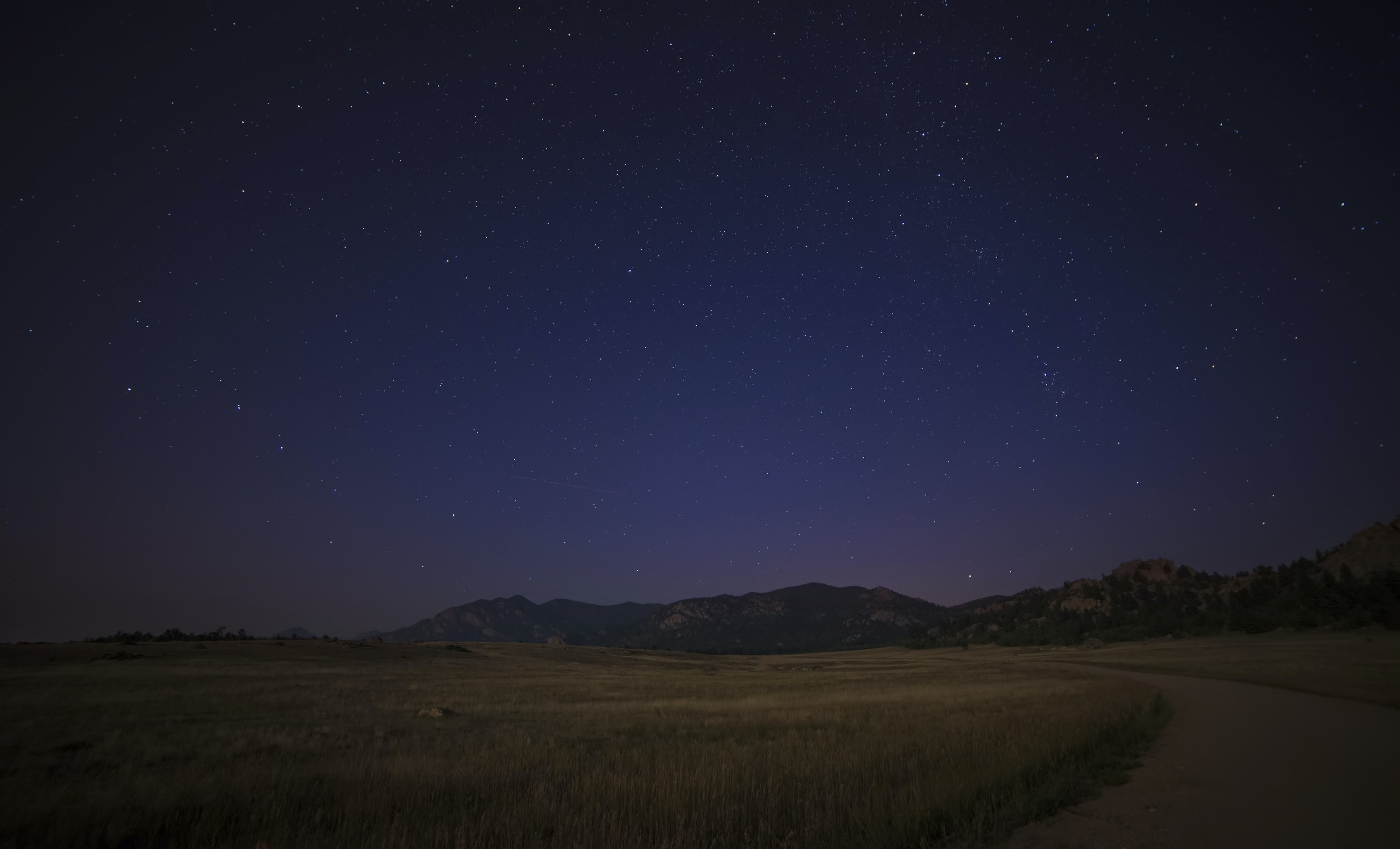 A country road with mountains in the distance under a starry night in Colorado.