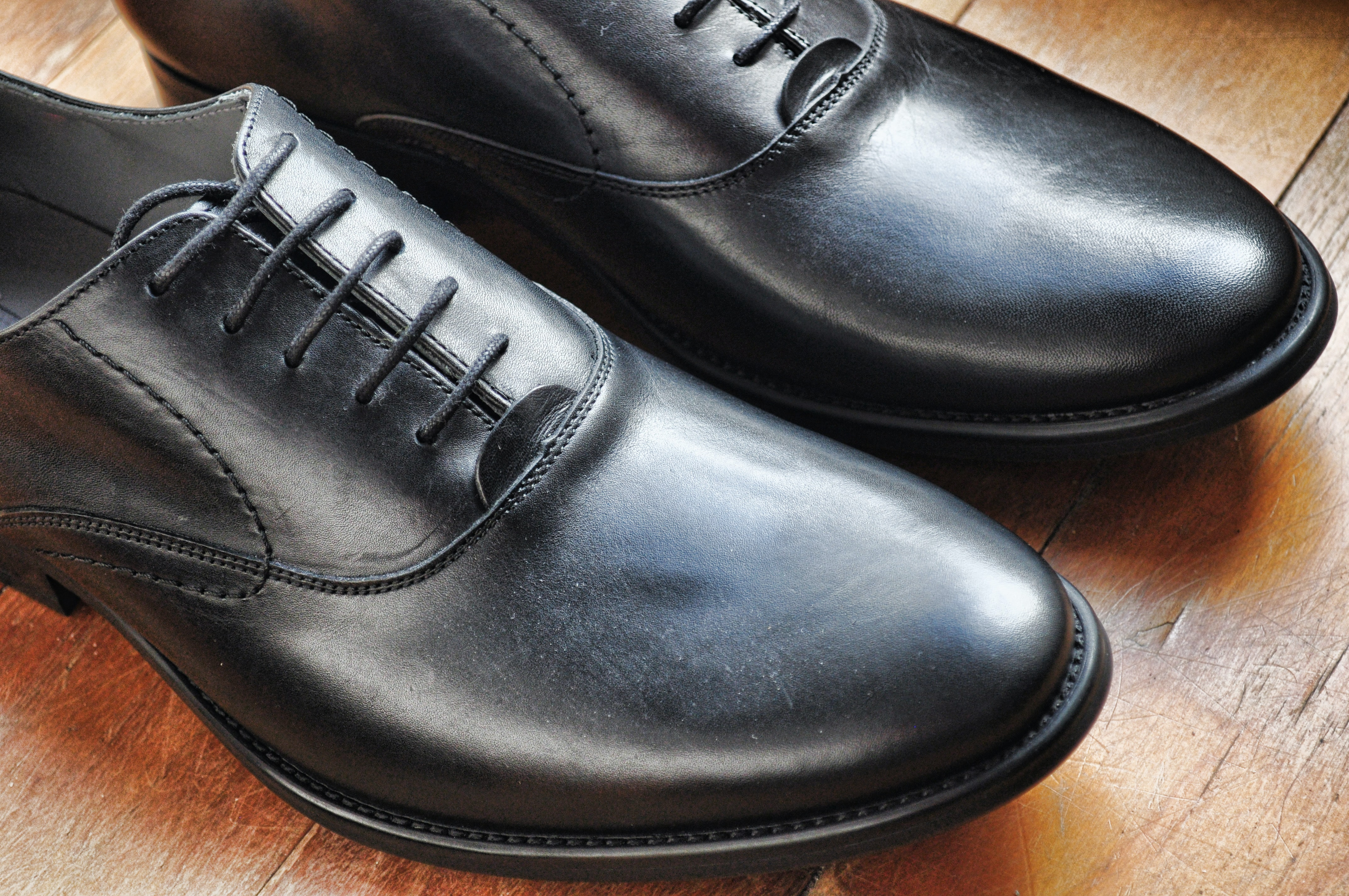 A close-up of a shiny pair of black leather shoes