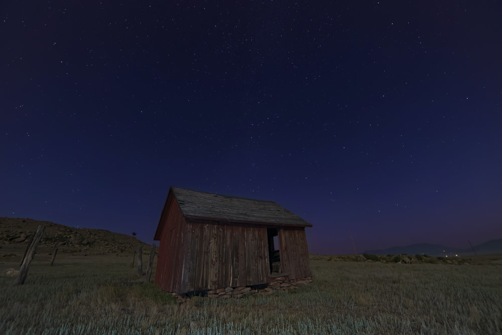 brown wooden shed on green grass field