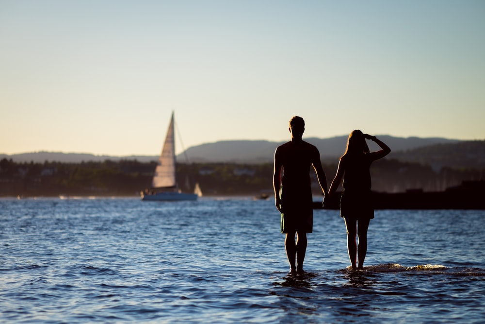 silhouette of man and woman on body of water at daytime