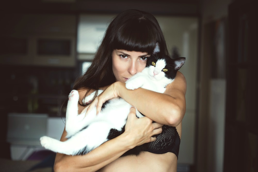 woman carrying cat