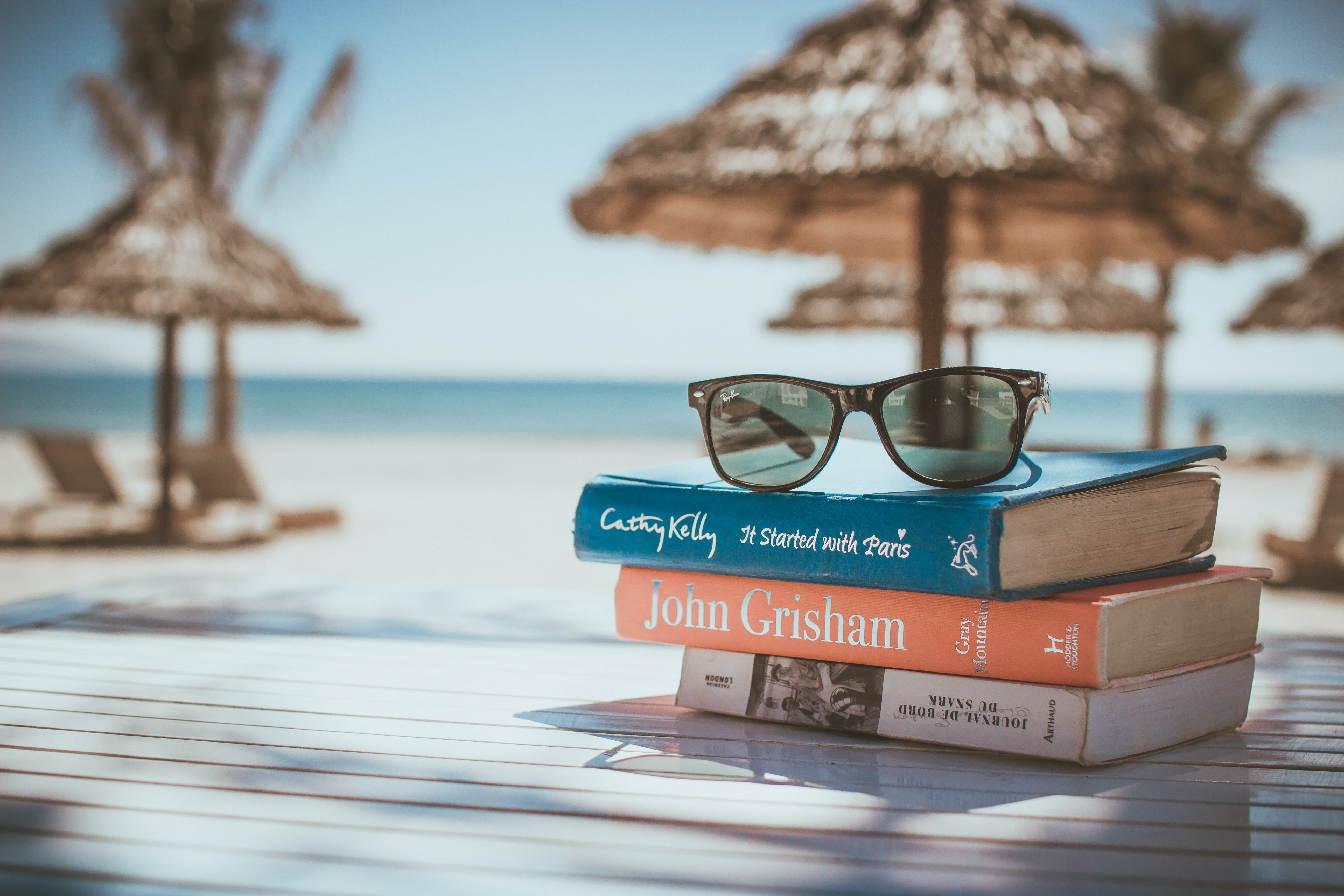 A pair of sunglasses is on top of books by famous authors on a beach table.