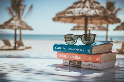 black framed ray-ban wayfarer sunglasses on top of book holiday teams background