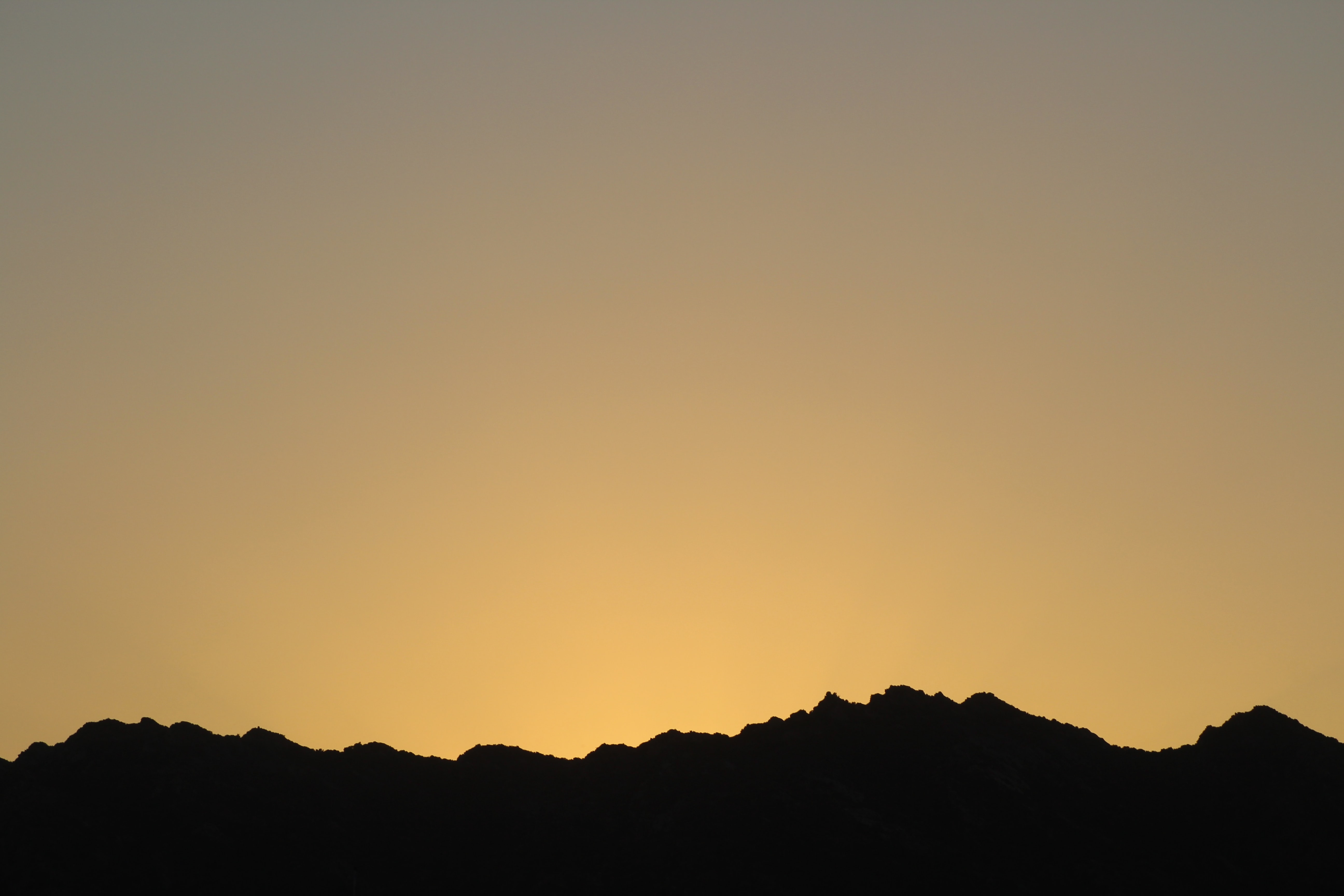 silhouette of mountains with sunrise background