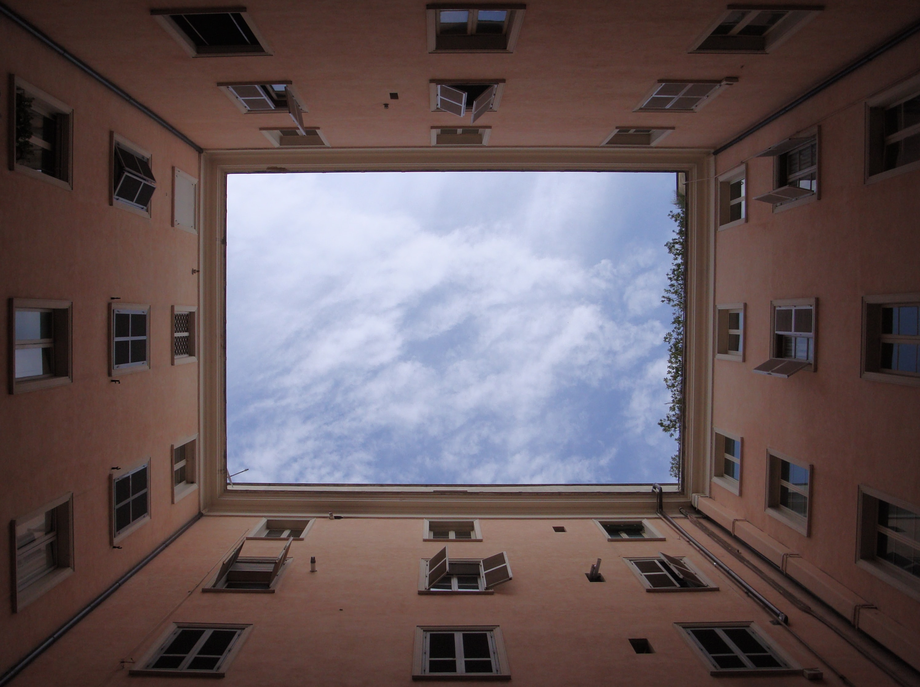Scattered clouds in the sky framed by the well of an apartment building in Rome