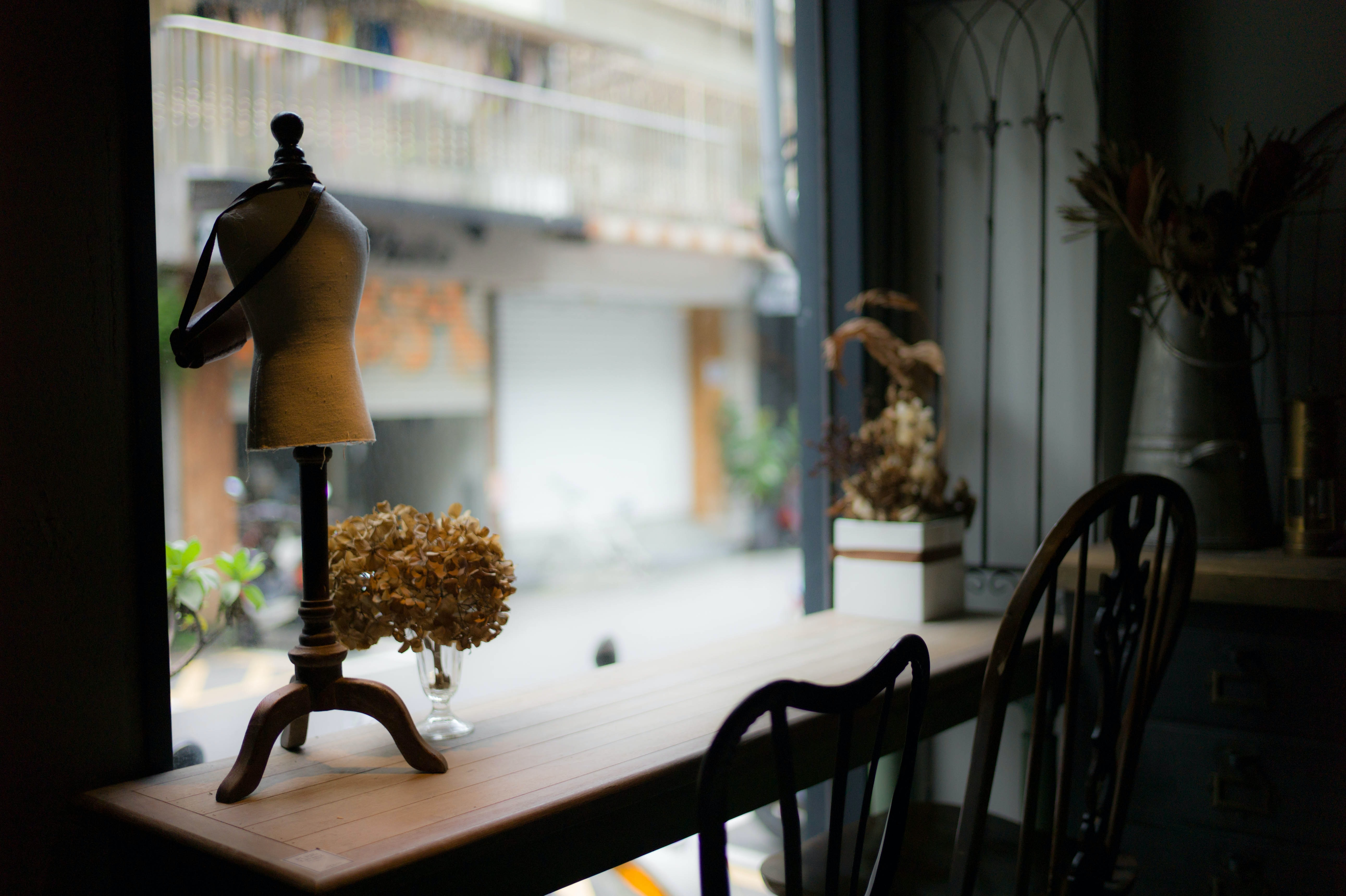 A narrow table with dried flowers on it near a store window