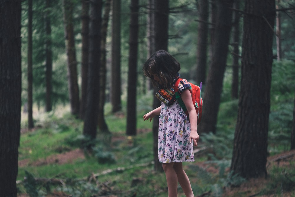 girl walking in field surrounded with tall and green trees