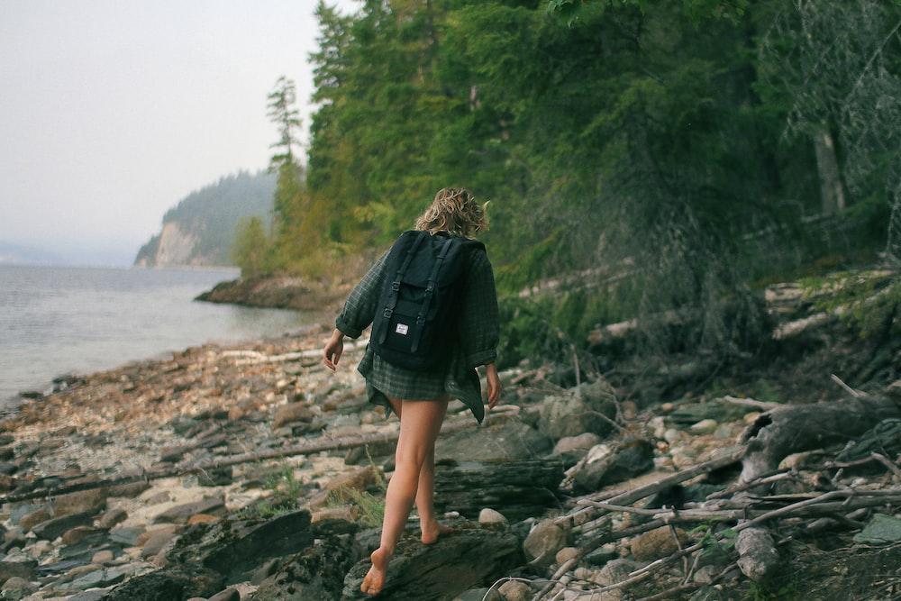 woman walking on rocky seashore