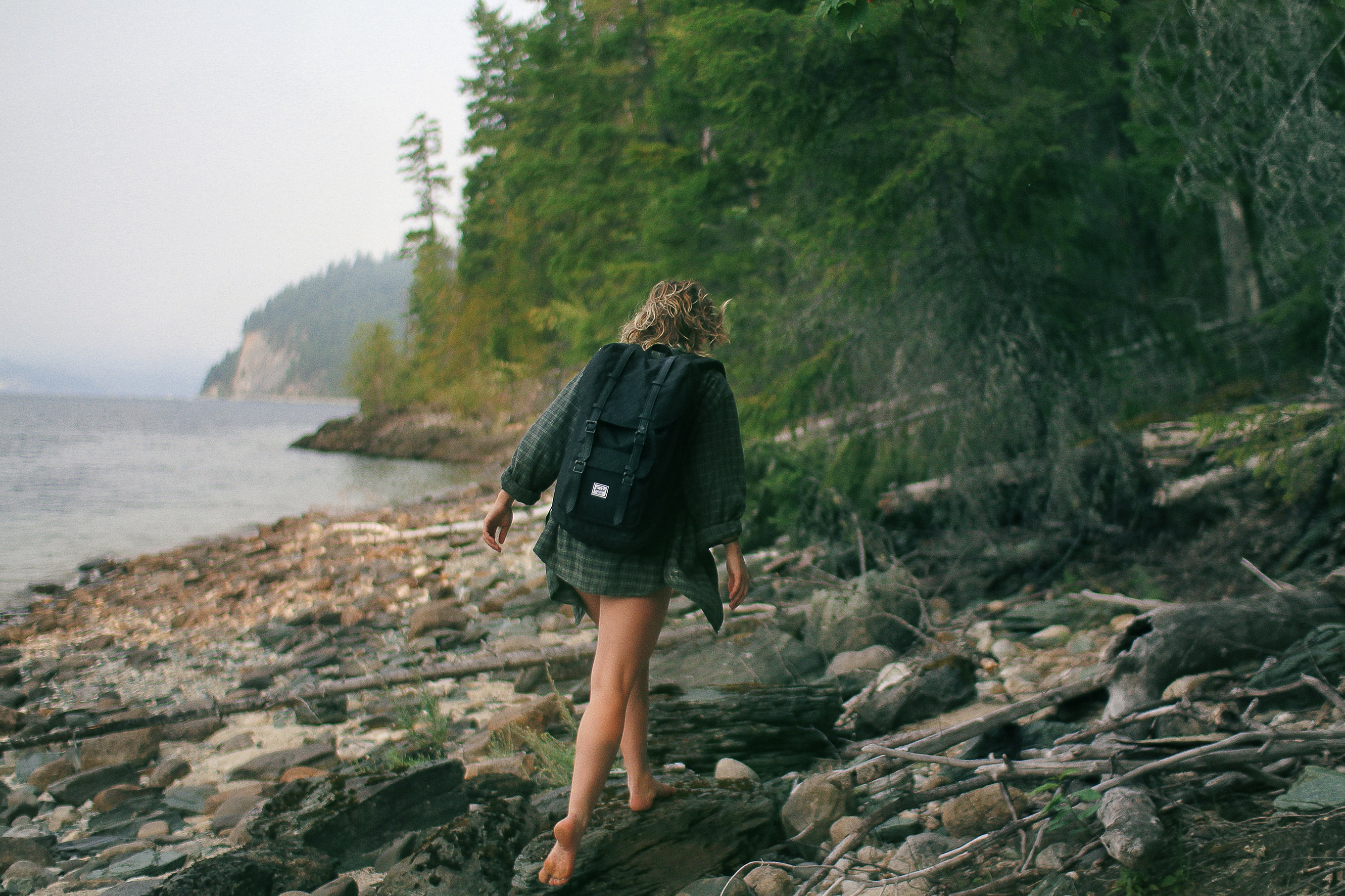 woman walking on rocky seashore