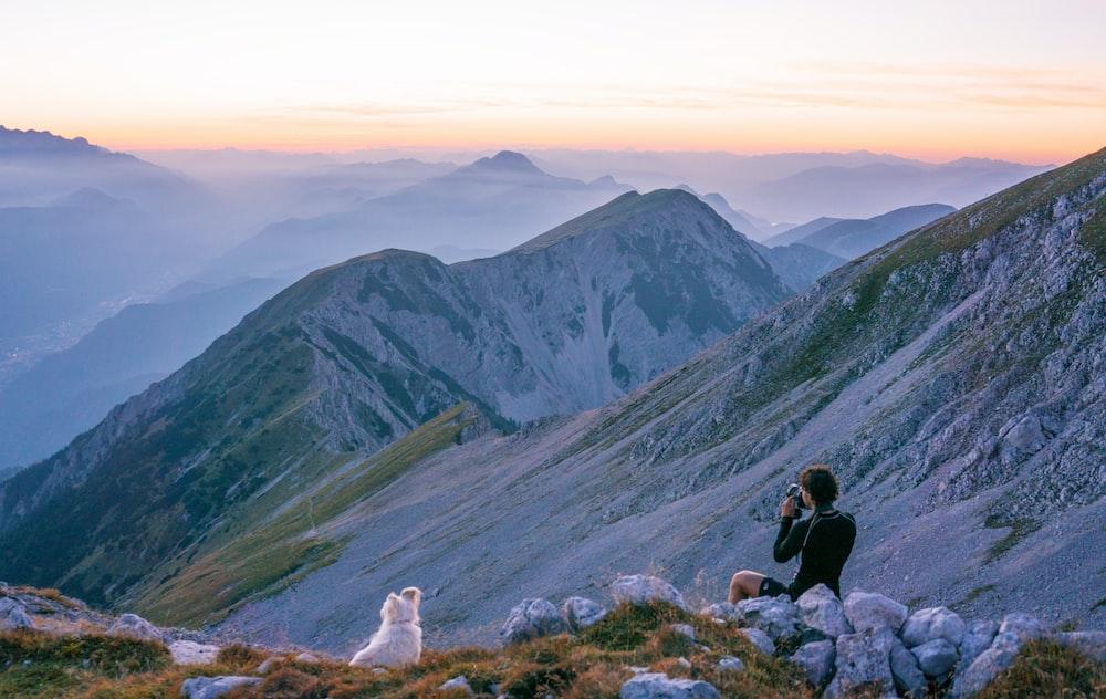 person sitting on mountain near white dog during daytime