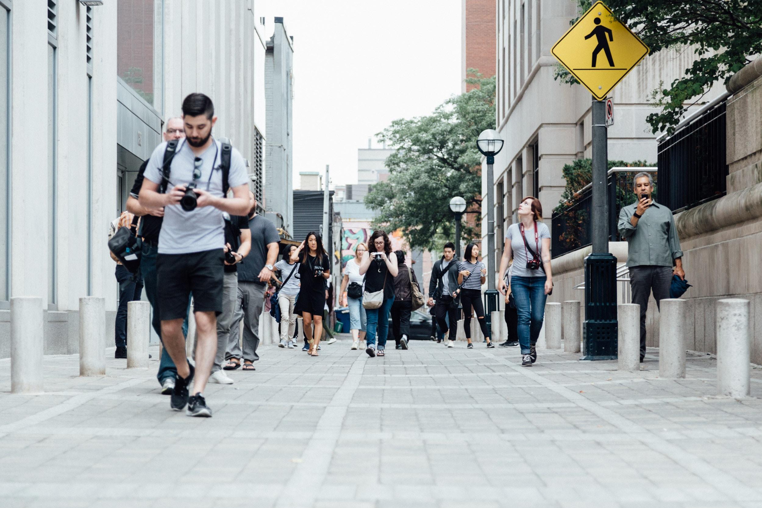 A diverse group of pedestrians walks down a sidewalk in Toronto