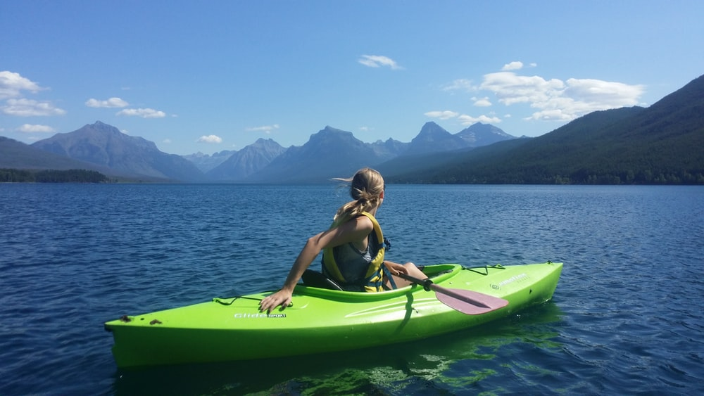 woman on kayak in the middle of body of water