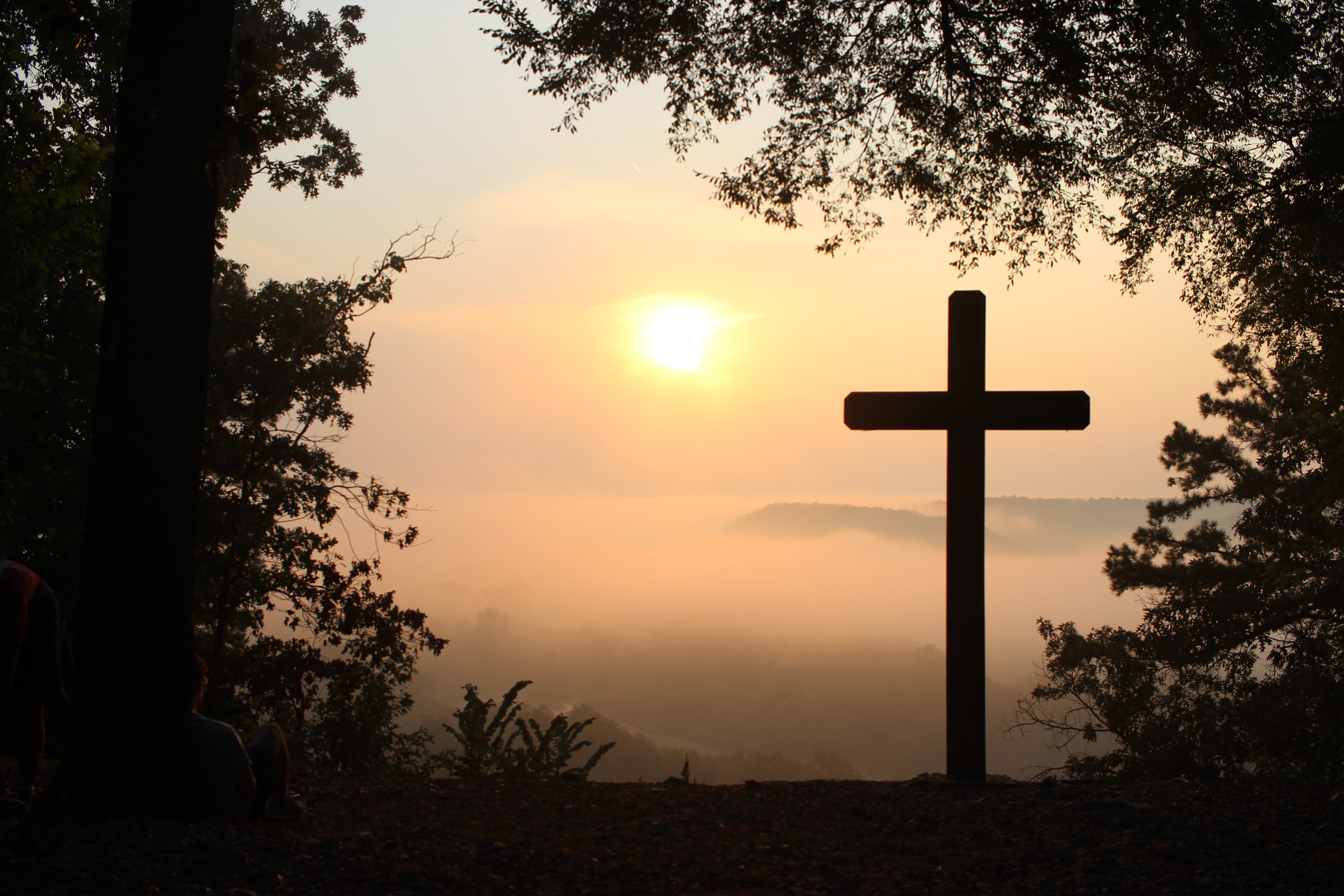 A silhouette of a cross in front of a sunset.