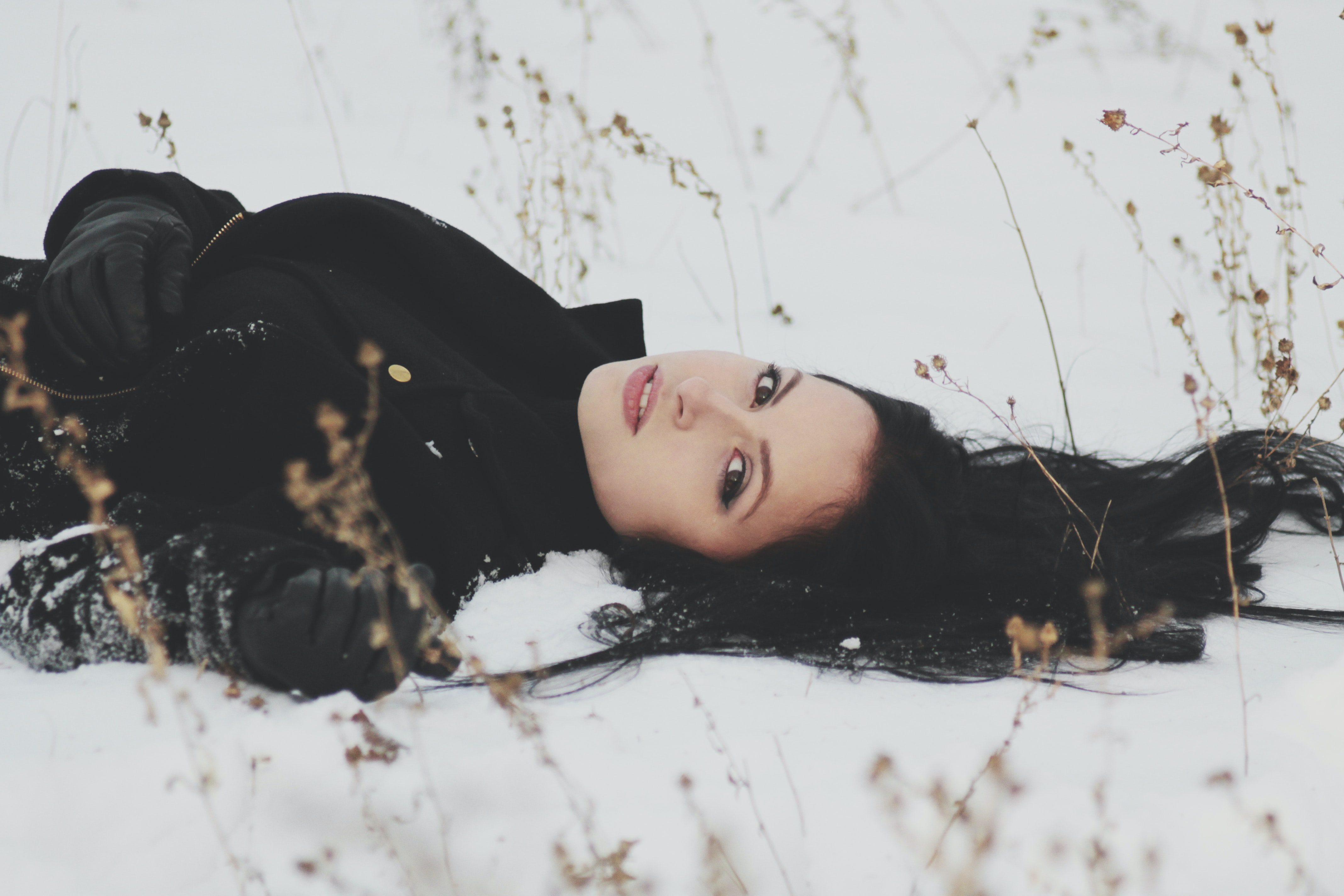 Woman laying down in a field of snow alone