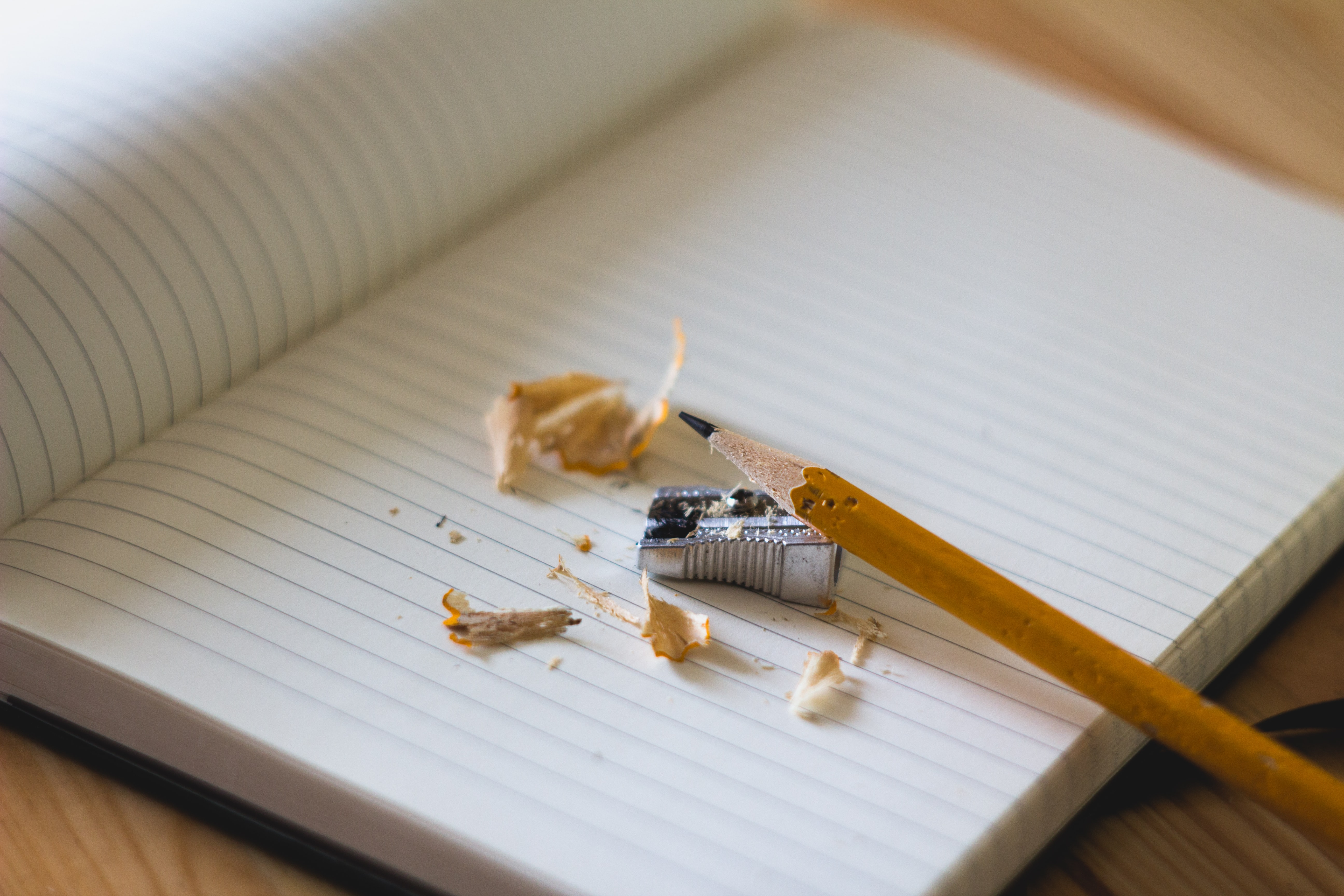 Pencil shavings around a pencil and a pencil sharpener on an open notebook