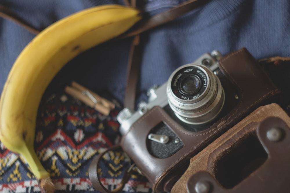 selective focus photography of camera beside banana