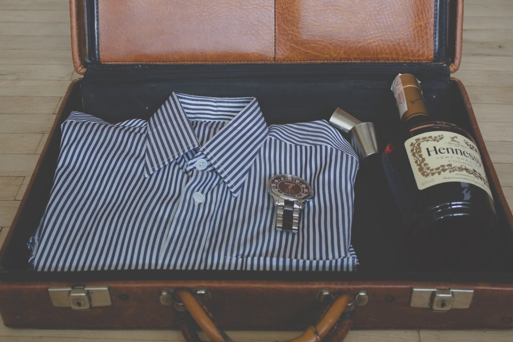 An open suitcase with clothes, a watch, shot glasses and a bottle of Hennessy.
