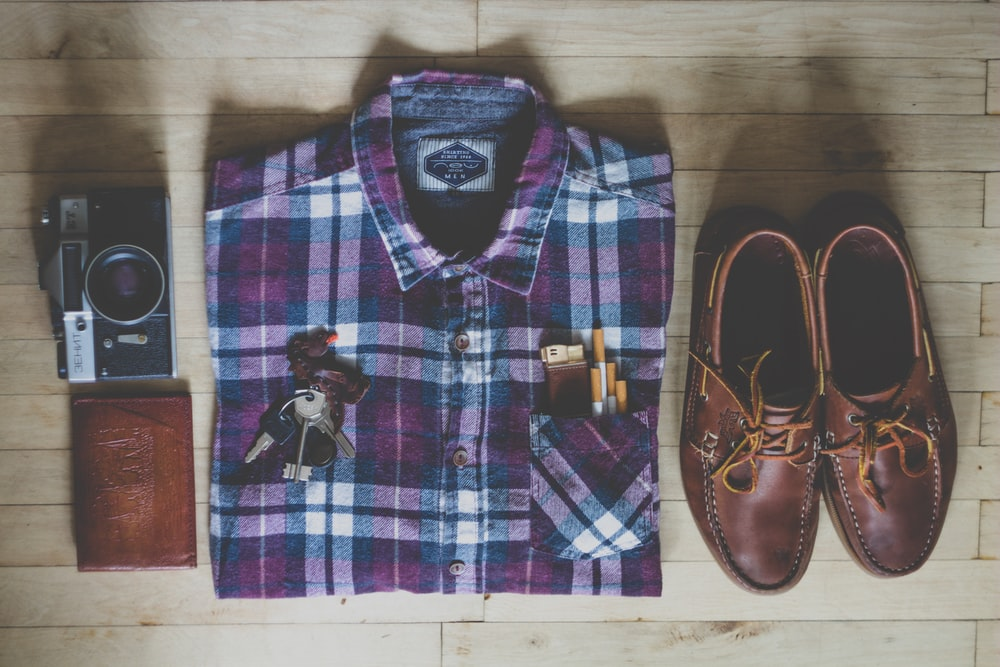 flat lay photography of button-up shirt, camera, keys, cigarettes, and pair of brown leather boat shoes