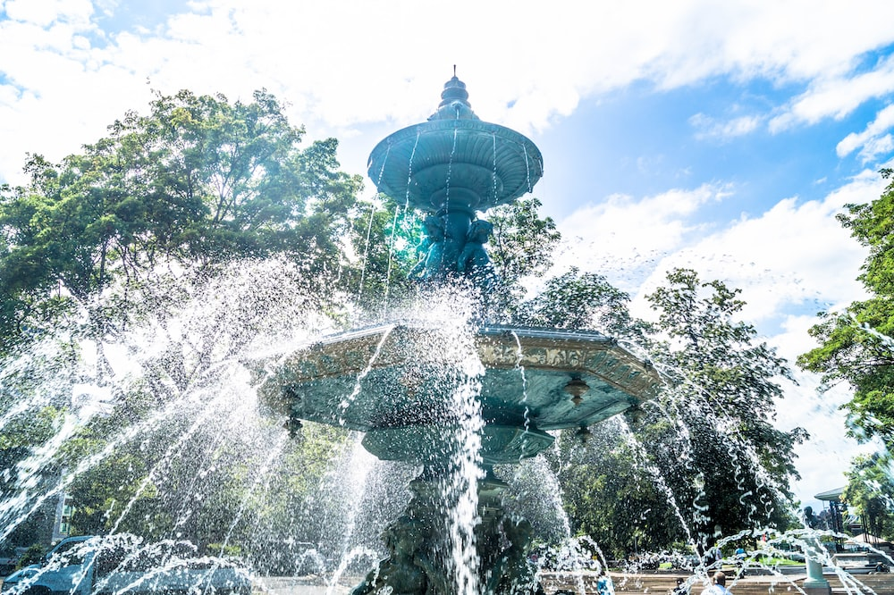 shallow focus photo of outdoor fountain under white and blue cloudy sky