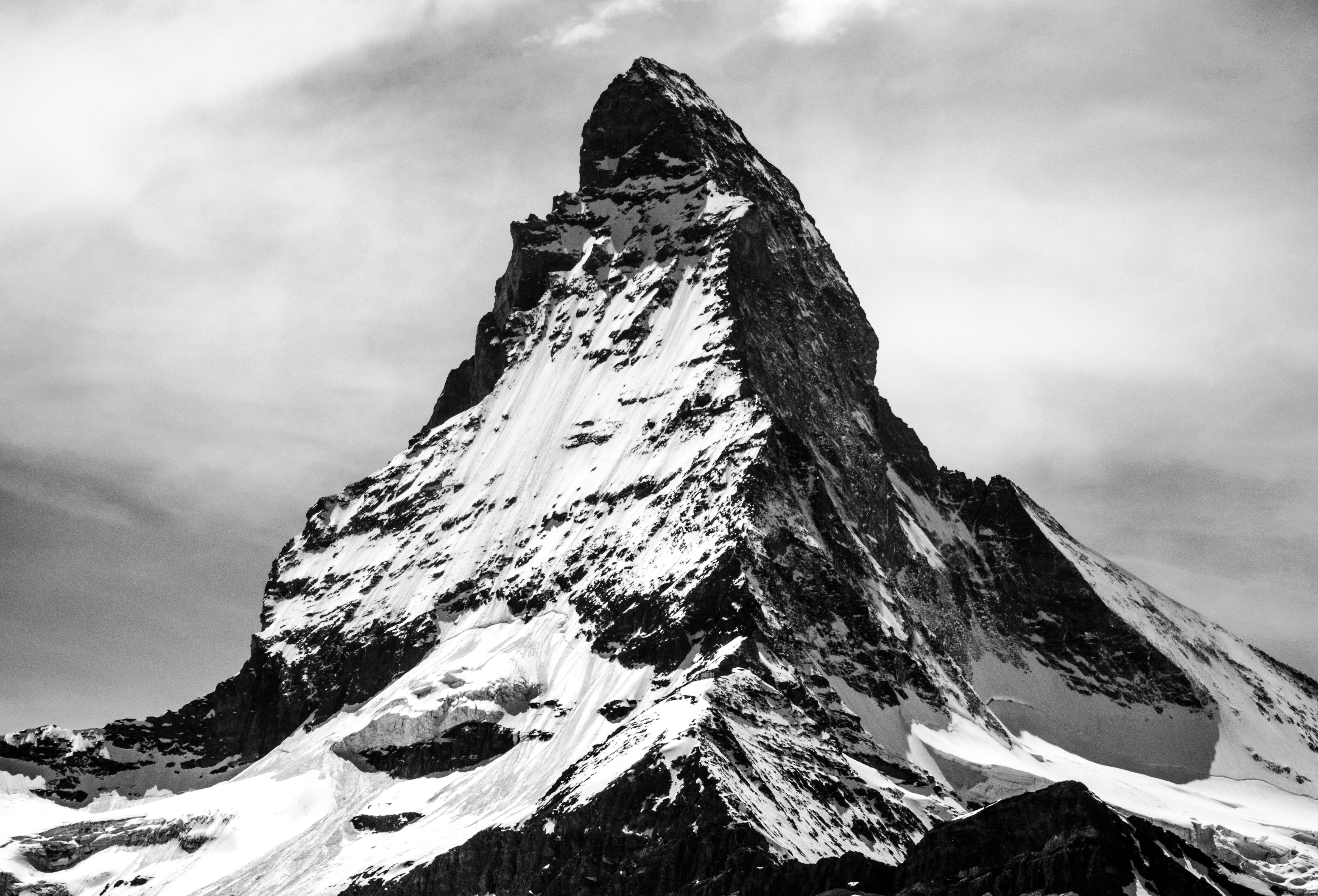 A black and white photo of a peak covered in snow in Zermatt.