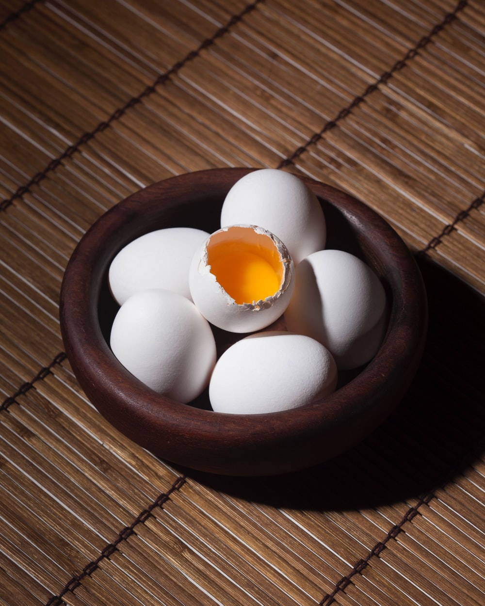 One egg cracks to show the yolk in a bowl full of eggs