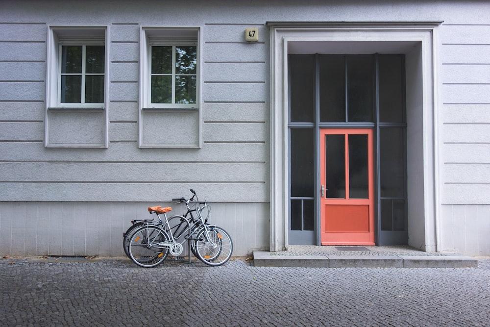 two assorted bicycles near orange door